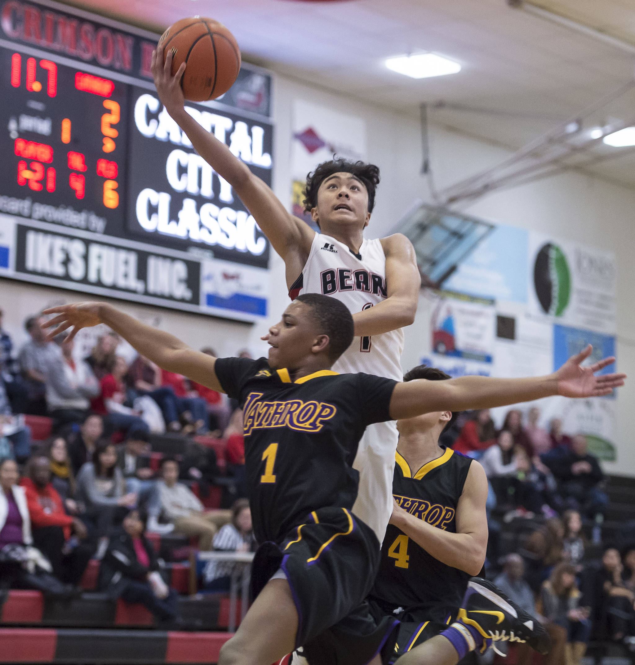 Juneau-Douglas' Israel Yadao lays the ball up over Lathrop's Jakobee Johnson at the Princess Cruises Capital City Classic at Juneau-Douglas High School on Thursday, Dec. 27, 2018. Juneau-Douglas won 69-45. (Michael Penn | Juneau Empire)