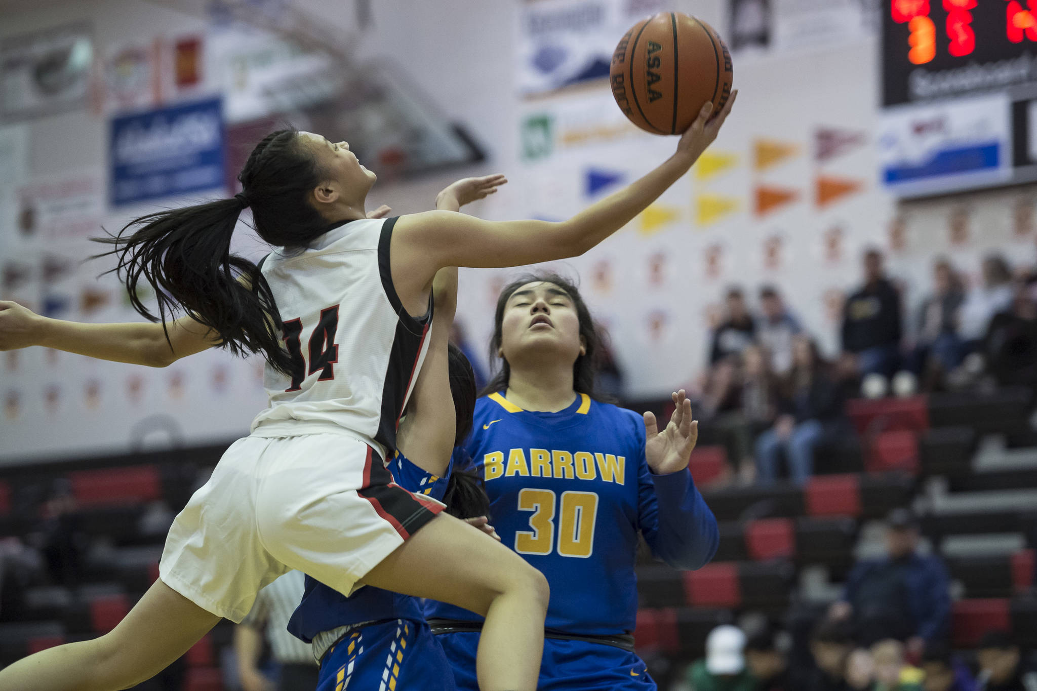 Juneau-Douglas' Alyxn Bohulano, left, drives to the basket against Barrow's Trinity Manu at the Princess Cruises Capital City Classic at Juneau-Douglas High School on Friday, Dec. 28, 2018. (Michael Penn | Juneau Empire)