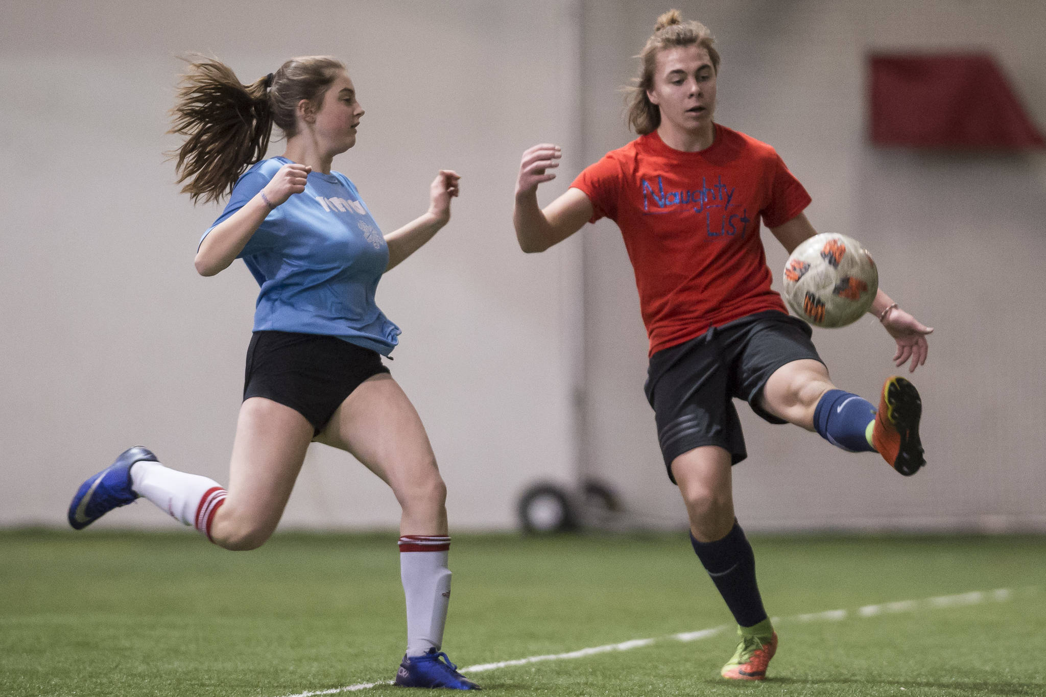 Iced Out, blue, competes against Naughty List, red, in the finals of the high school division at the annual Holiday Cup Soccer Tournament at the Wells Fargo Dimond Park Field House on Monday, Dec. 31, 2018. Iced Out won 8-2. (Michael Penn | Juneau Empire)
