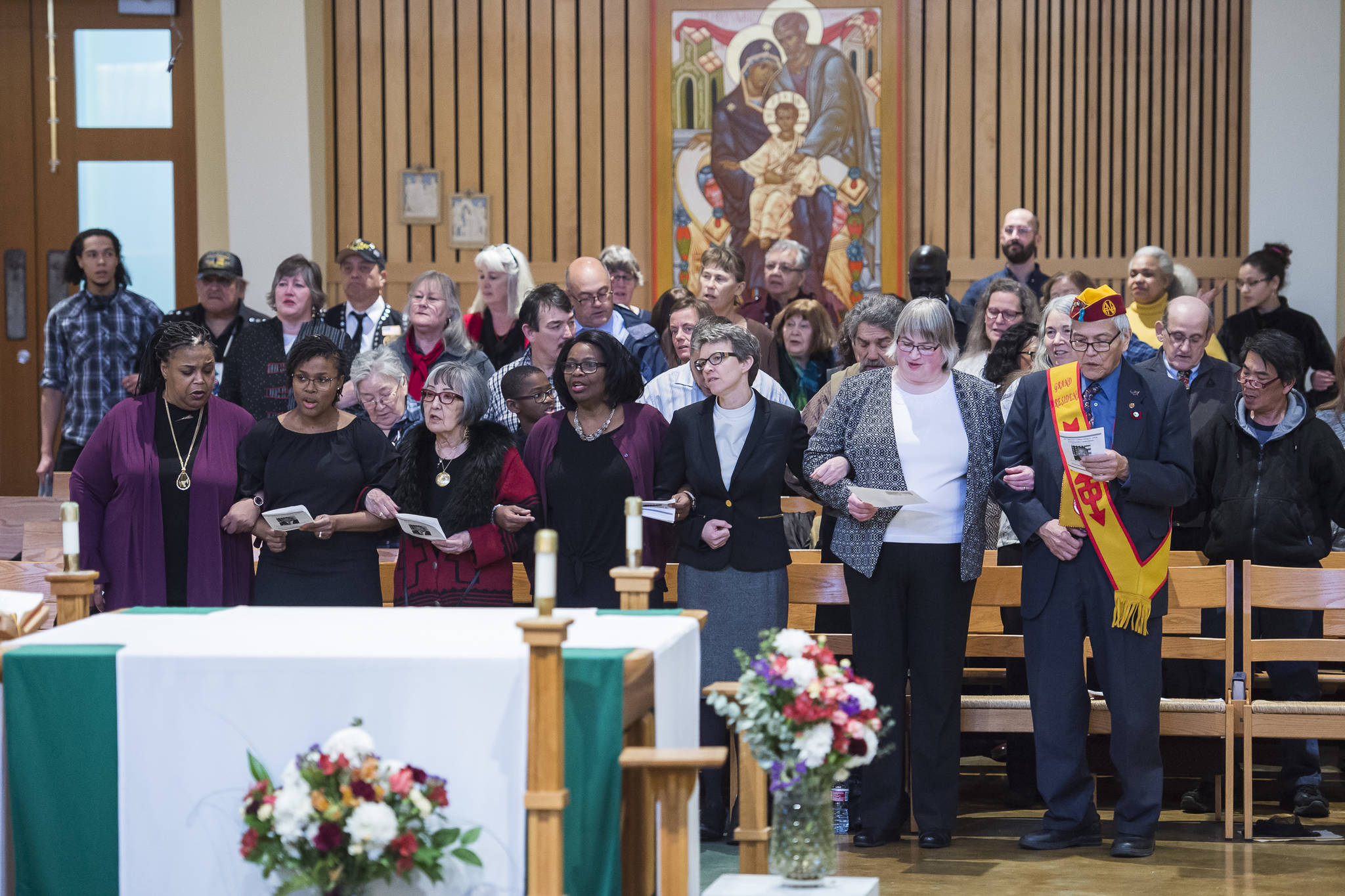 "Juneau residents link arms as they sing ""We Shall Overcome"" at the Dr. Martin Luther King Jr. 2019 Community Celebration at St. Paul's Catholic Church on Monday, Jan. 21, 2019. (Michael Penn 