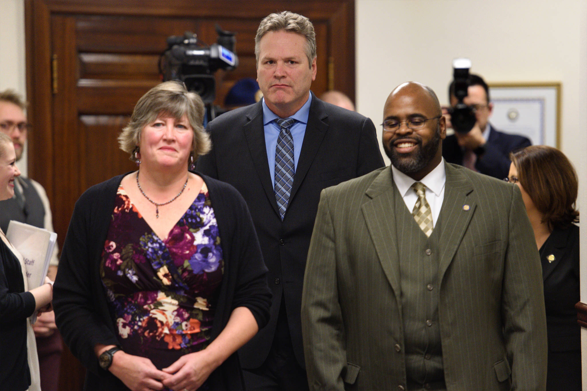 Gov. Mike Dunleavy walks into his State of the State speech in the House chamber at the Capitol in Juneau, Alaska, as Rep. Sara Hannan, D-Juneau, left, and Sen. David Wilson, R-Wasilla, walk into a Joint Session of the Alaska Legislature on Tuesday, Jan. 22, 2019. (Michael Penn | Juneau Empire)