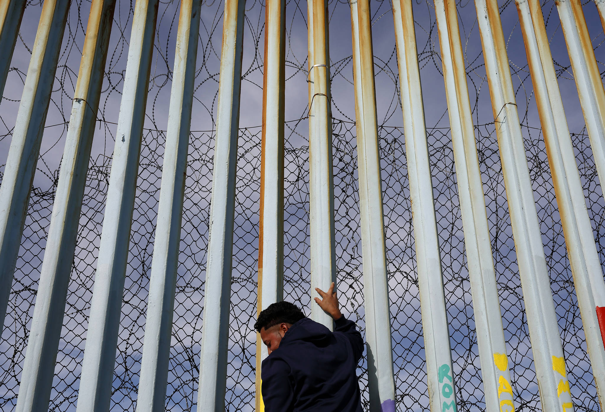 In this Jan. 8, 2019 photo, a man holds on to the border wall along the beach, in Tijuana, Mexico. The migrant caravan that was seized upon by U.S. President Donald Trump in the run-up to the 2018 election has quietly dwindled to a few hundred people, with many of them having crossed into the U.S. or put down roots in Mexico. (Gregory Bull | Associated Press)