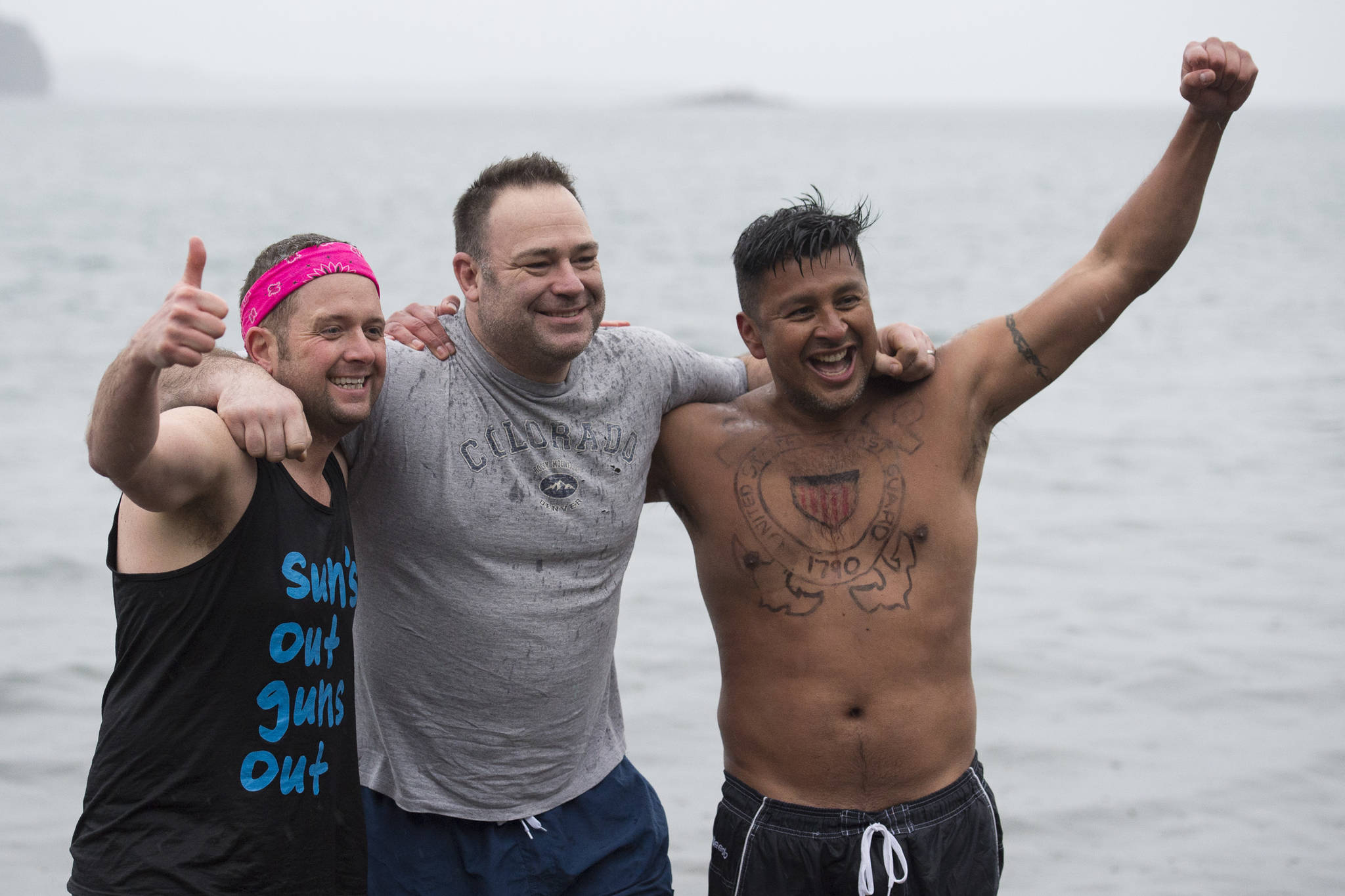 U.S. Coast Guard members John Dale, left, Chris Coutu, center, and Marvin Pena pose for a picture before taking to the frigid waters at Auke Bay Recreation Area for the annual Juneau Polar Bear Dip on Tuesday, Jan. 1, 2019. Nearly 200 people took the plunge to start off the new year. (Michael Penn | Juneau Empire)