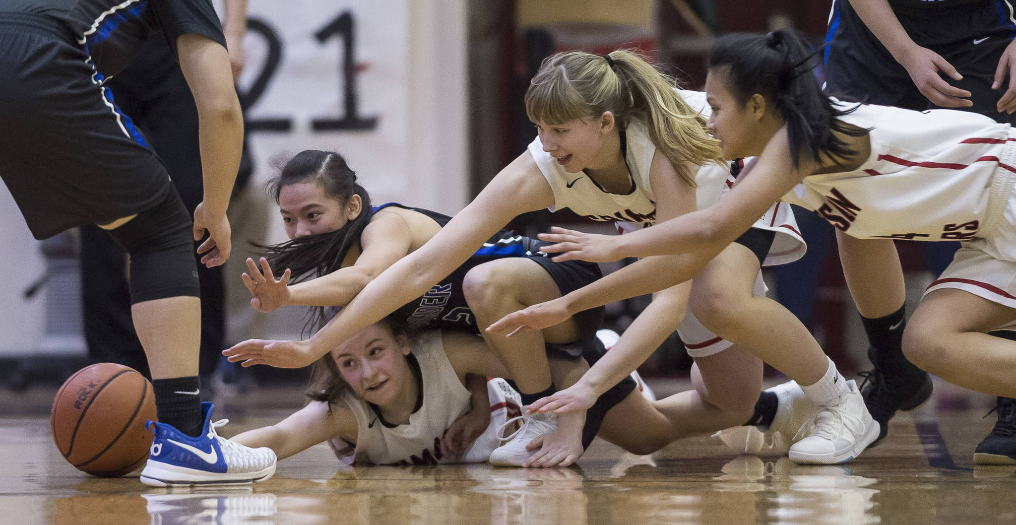 Thunder Mountain's Kyaye Garcia, left, dives for a loose ball against Juneau-Douglas' Kiana Potter, bottom left, Caitlin Pusich and Alyxn Bohulano, right, at JDHS on Friday, March 3, 2018. JDHS won 53-33.