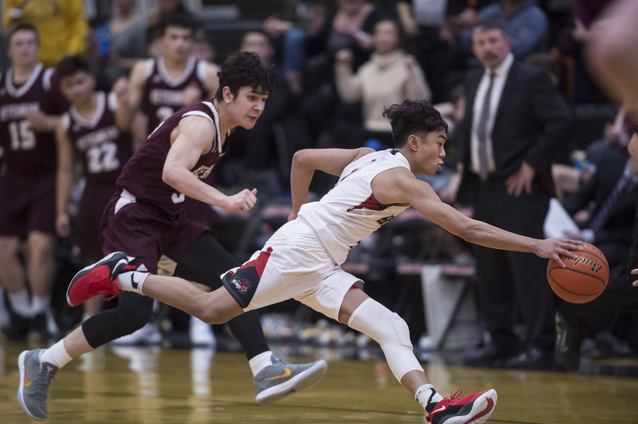 Juneau-Douglas' Israel Yadao, right, races Ketchikan's James Nordlund down the court at JDHS on Friday, Jan. 11, 2019. JDHS won 75-67. (Michael Penn | Juneau Empire)