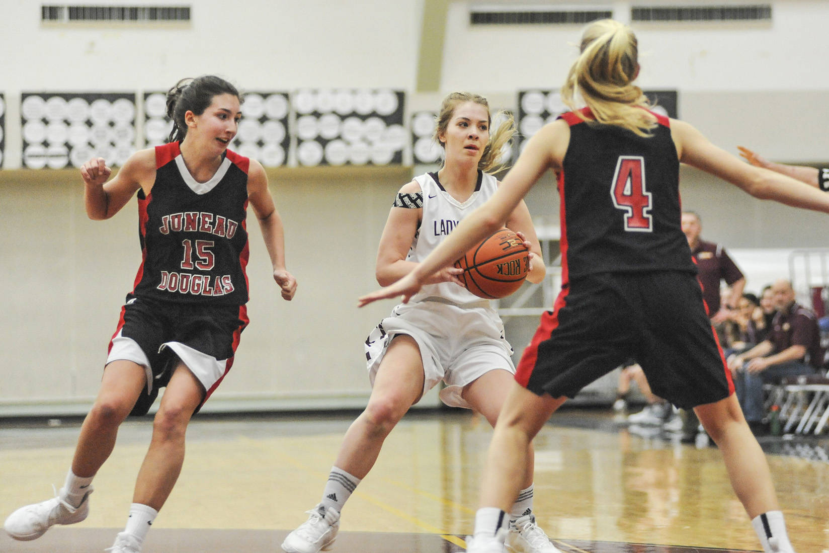 Juneau-Douglas players Jenae Pusich, left and Sadie Tuckwood, right, put the pressure on Kayhi's Ashley Huffine in the first quarter Friday night at the Clarke Cochrane Gymnasium. JDHS won 50-35 over the Lady Kings. (Hall Anderson | Ketchikan Daily News)