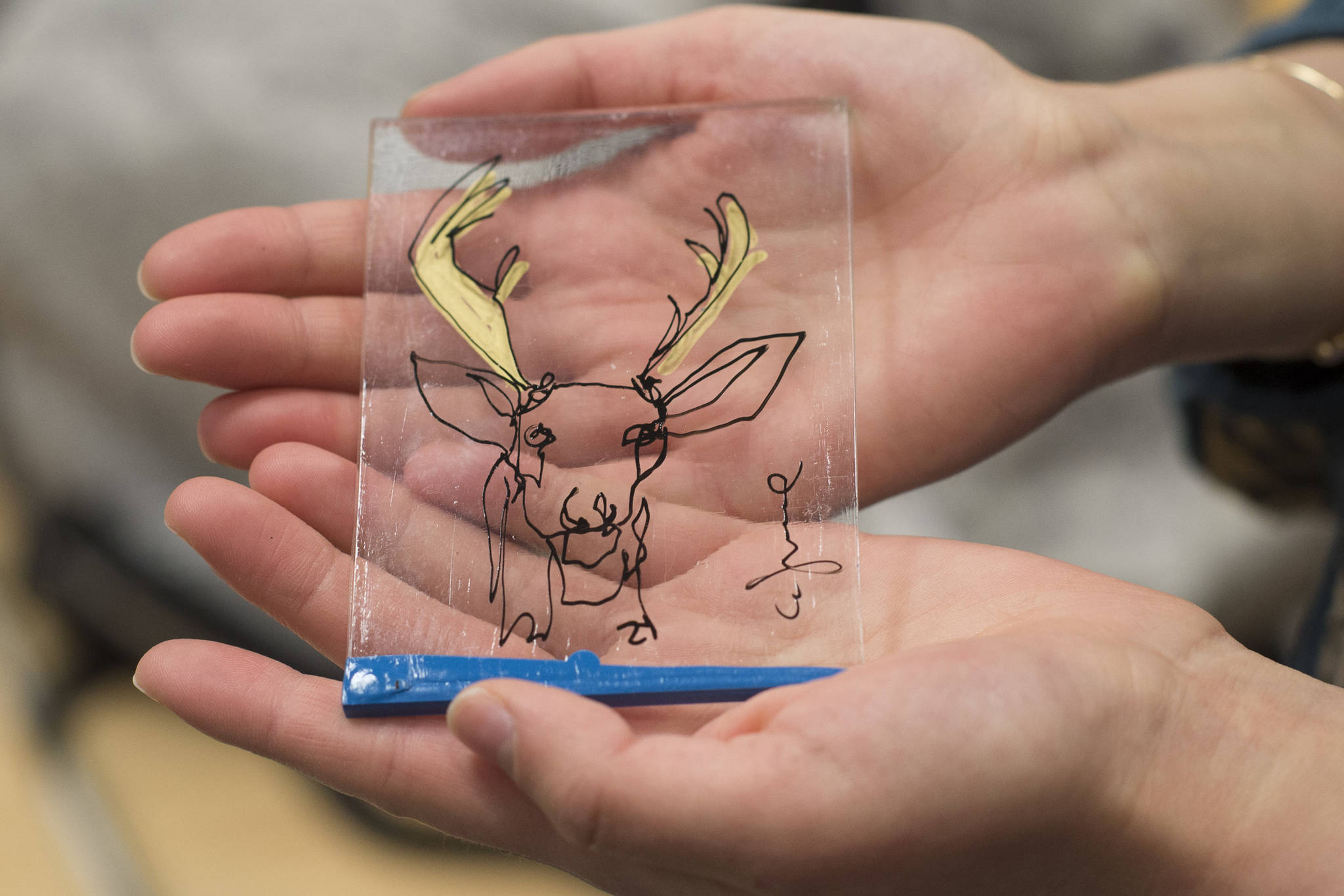 Thunder Mountain High School junior Madison Kahle holds a signed drawing of a deer's head on plexiglass by professional contour artist Ian Sklarsky. (Michael Penn | Juneau Empire)