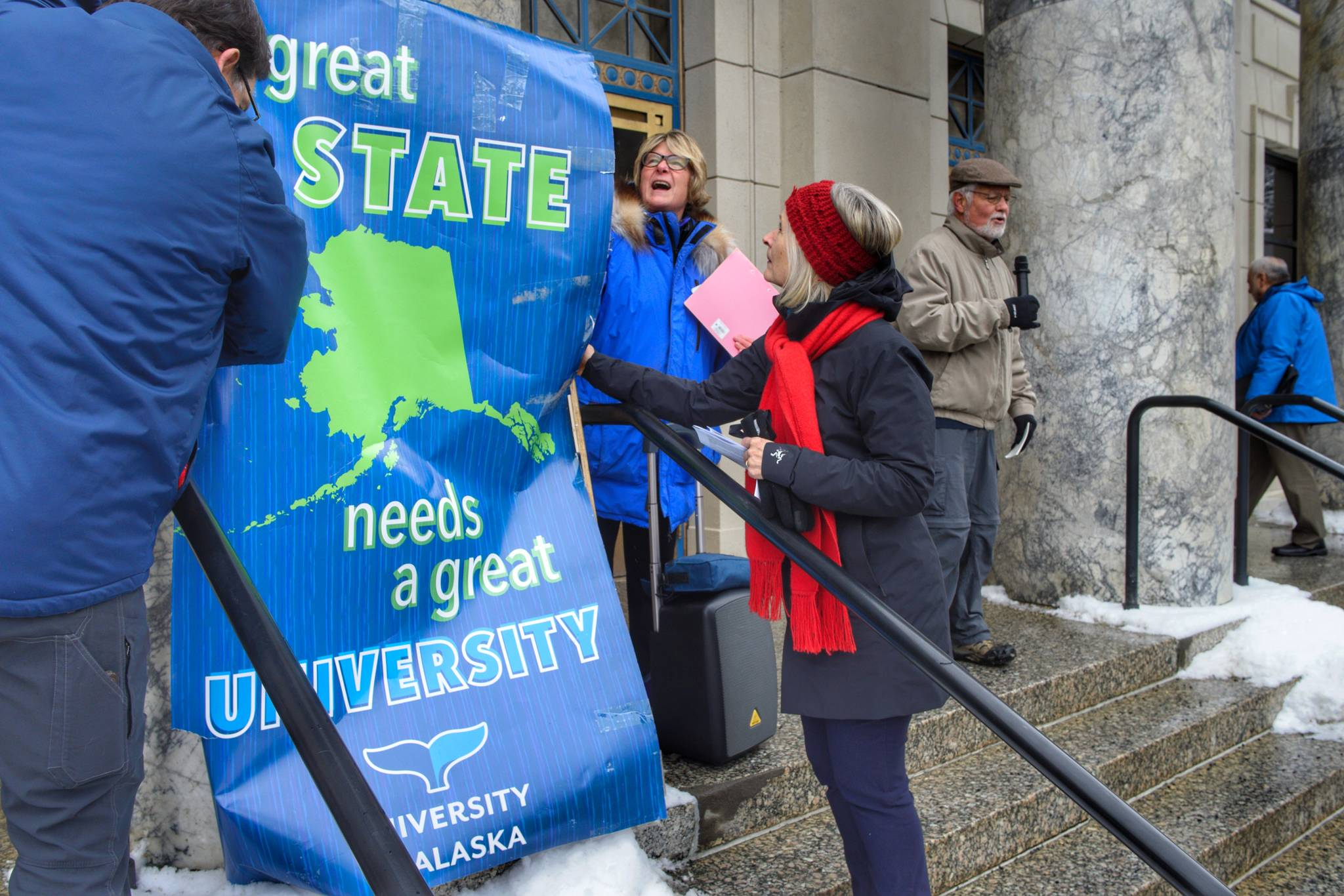 University of Alaska Southeast Instructor Jim Powell, left, his wife, former Rep. Beth Kerttula, and Rep. Andi Story, D-Juneau, right, stand up a university sign as former Chancellor John Pugh speaks at a rally for funding the University of Alaska in front of the Capitol on Wednesday, Feb. 13, 2019. (Michael Penn | Juneau Empire)
