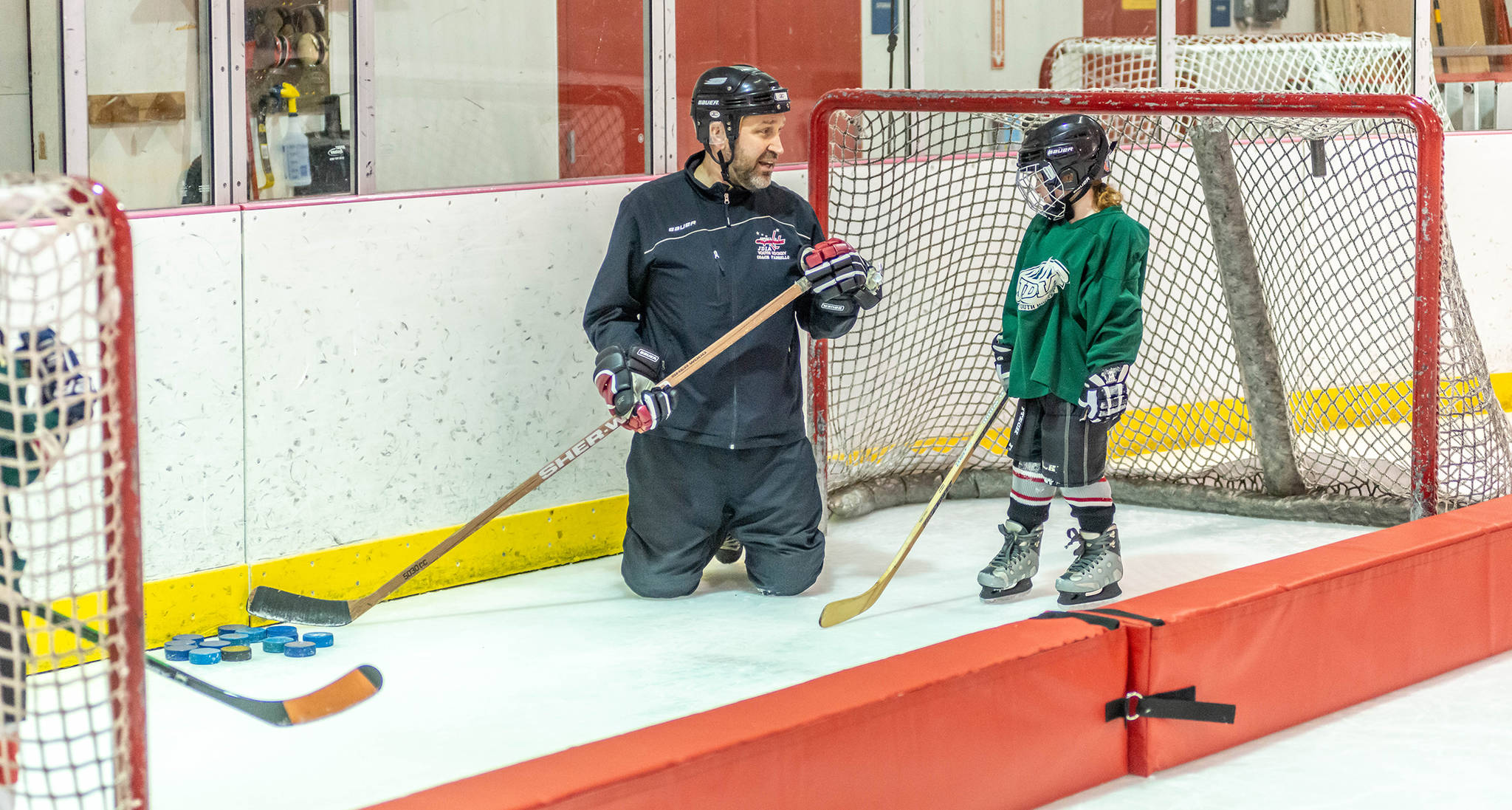 Coach Dan Fabrello shoots a quick smile at a JDIA youth player during a recent practice at Treadwell Ice Arena. (Courtesy Photo | Steve Quinn)