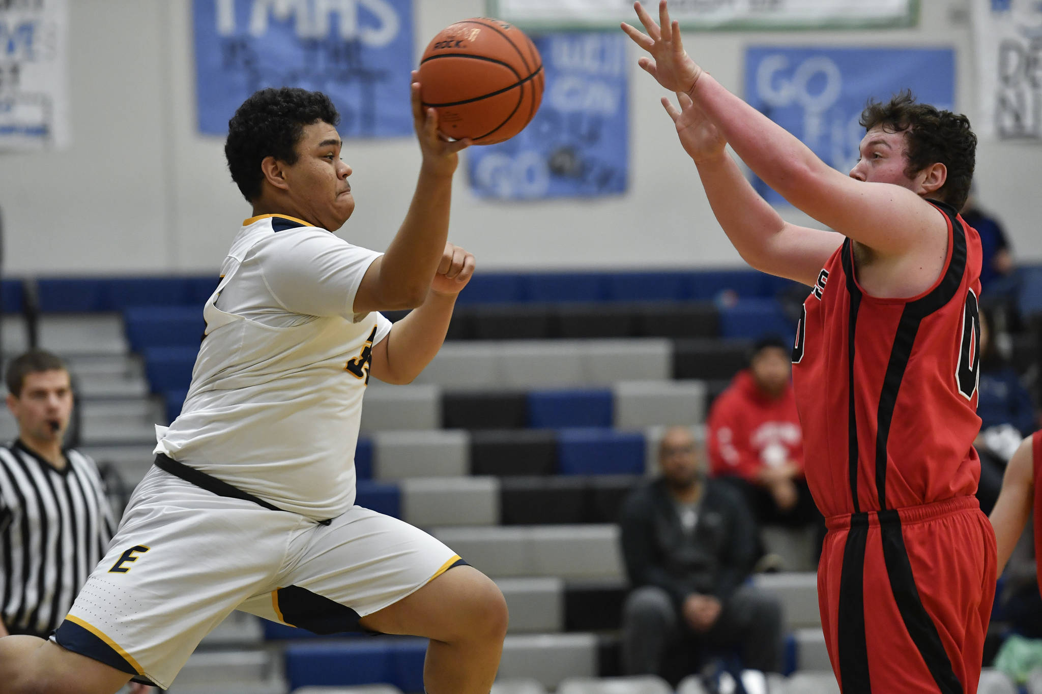 Angoon's Anthony Johnson passes against Gustavus' David Blaine at the Region V 1A Basketball Championships at Thunder Mountain High School on Thursday, Feb. 28, 2019. Angoon won 42-39. (Michael Penn | Juneau Empire)