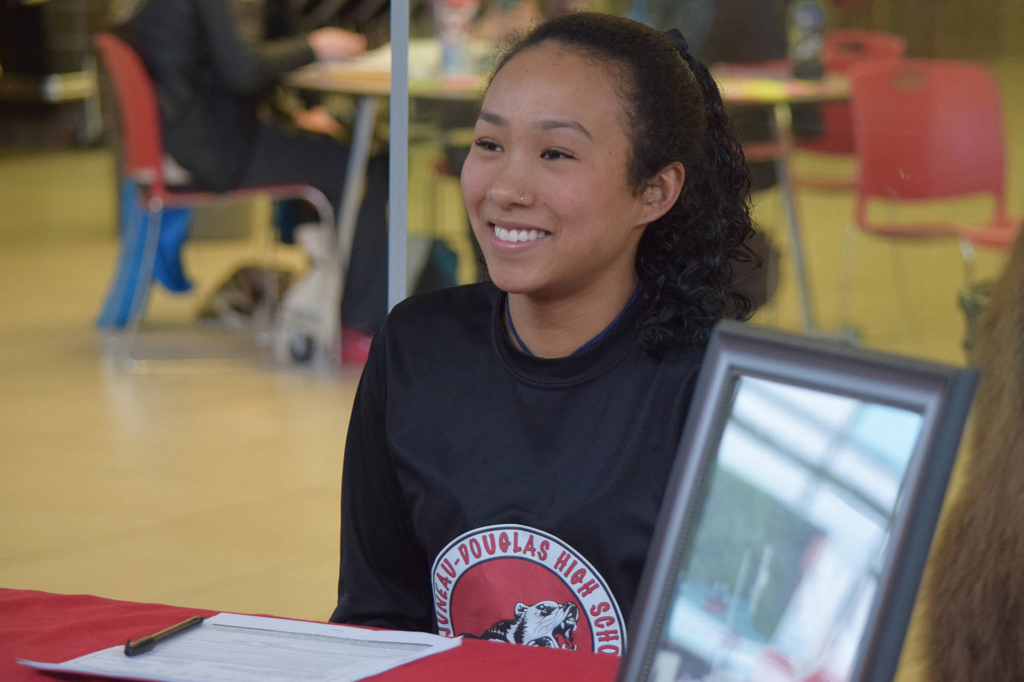 Juneau-Douglas High School senior Malia Miller finishes signing a National Letter of Intent with Bellevue College at the JDHS commons on Thursday, March 14, 2019. (Nolin Ainsworth | Juneau Empire)