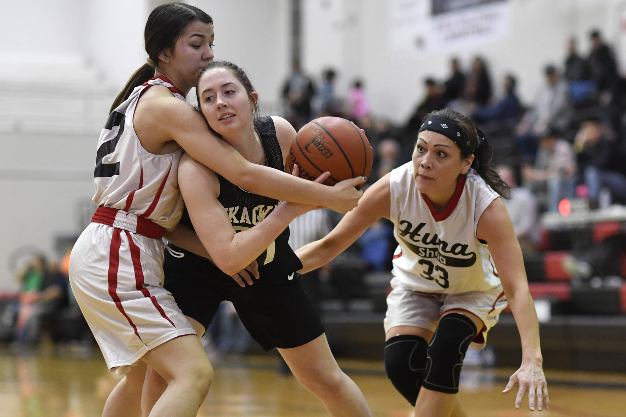 Skagway's Hailey Jensen, center, is closely guarded by Hoonah's Ronnie Roberts, left, and Krissy Benn at the Juneau Lions Club 73rd Annual Gold Medal Basketball Tournament at Juneau-Douglas High School: Yadaa.at Kalé on Tuesday, March 19, 2019. Skagway won 80-42. (Michael Penn | Juneau Empire)