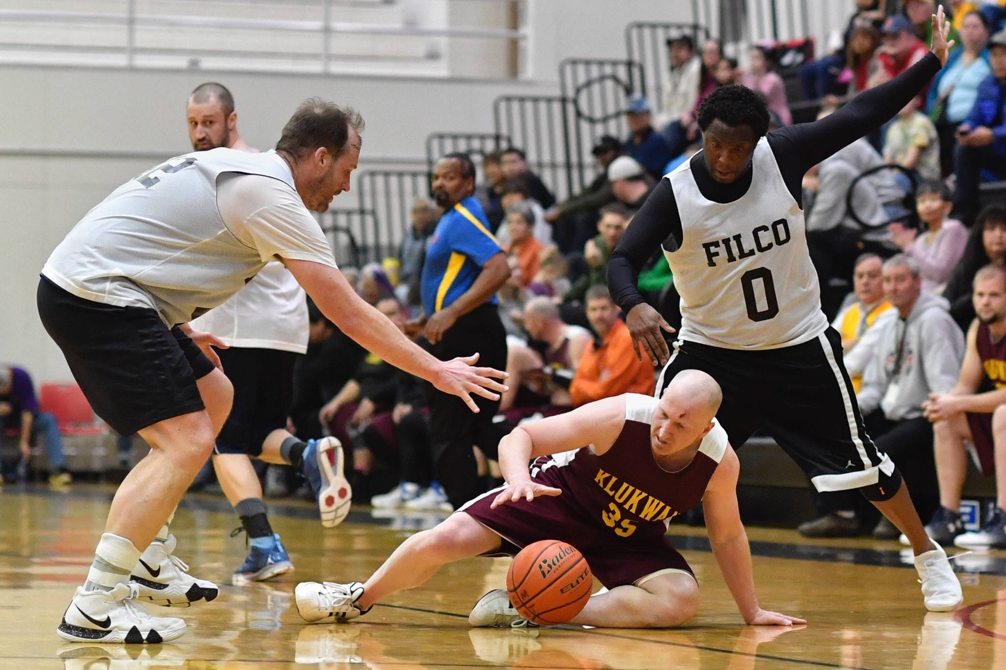 Klukwan's Brian Friske, center, goes for a loose ball against Filcom's Greg Lockwood, left, and Rob Ridgeway in their C bracket game at the Lions Club's Gold Medal Basketball Tournament on Thursday, March 21, 2019. (Michael Penn | Juneau Empire)