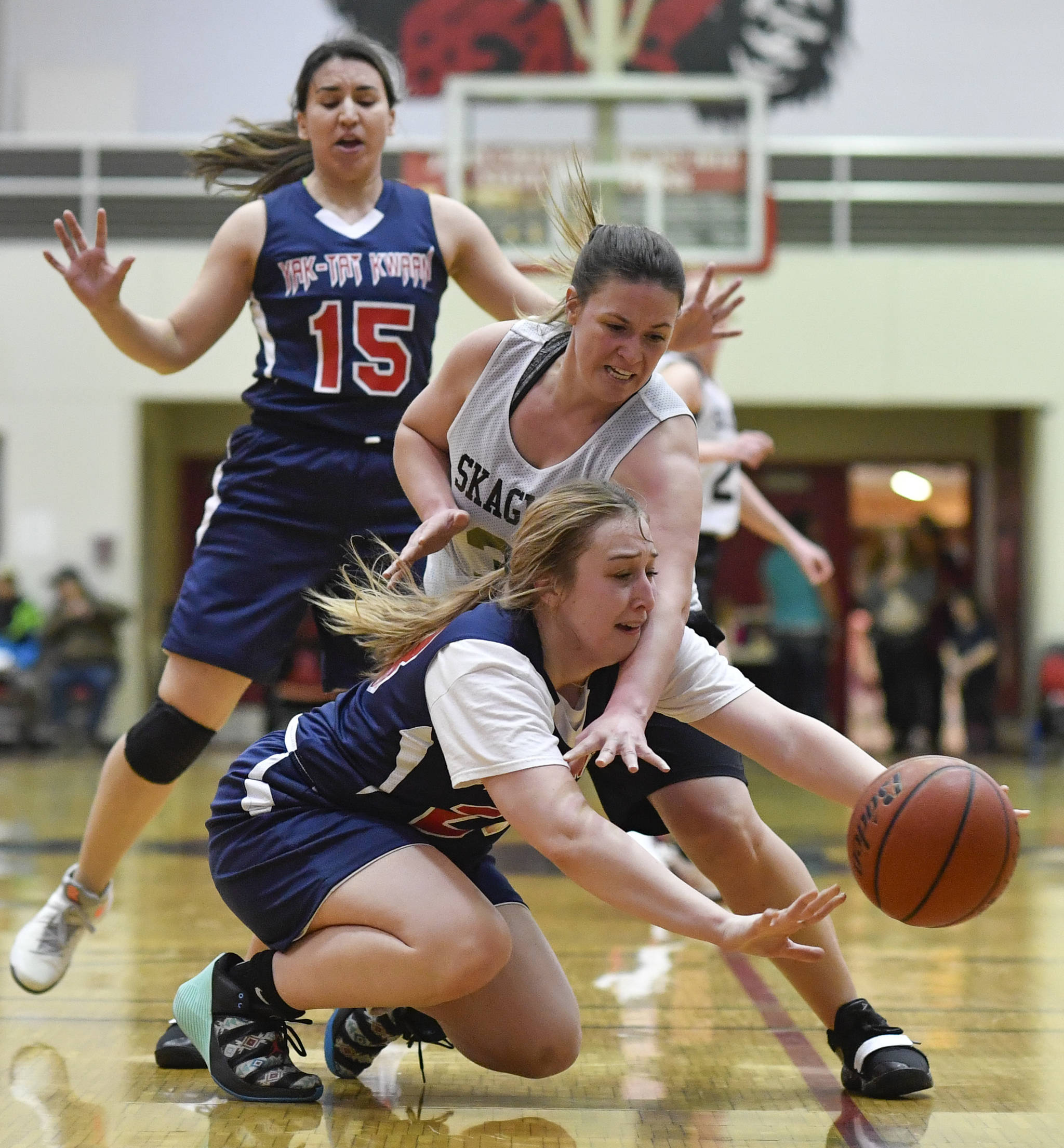 Yakutat's Janie Jensen, below, and Skagway's Tiffanie Ames dive for a loose ball during the women's bracket game at the Gold Medal Basketball Tournament on Thursday, March 21, 2019. (Michael Penn | Juneau Empire)