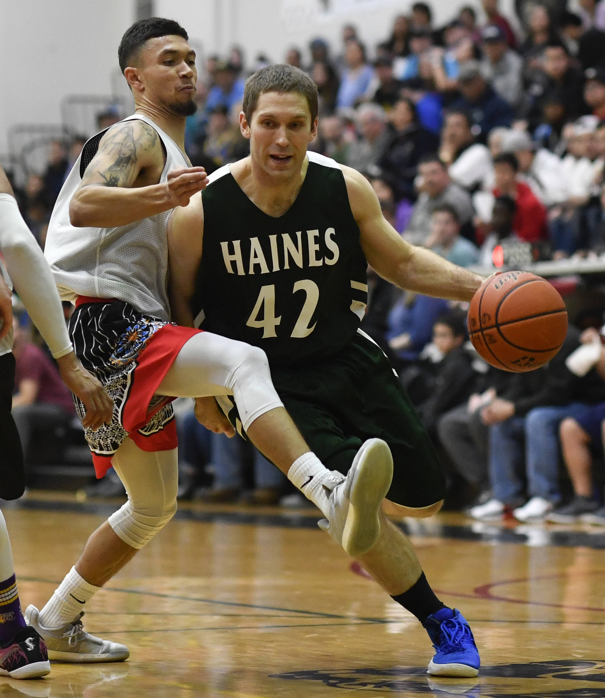 Angoon's Aquino Brinson attempts to stay in front of Haines' Kyle Fossman in the B final at the Gold Medal Basketball Tournament on Saturday, March 23, 2019. Haines won 88-80. (Michael Penn | Juneau Empire)