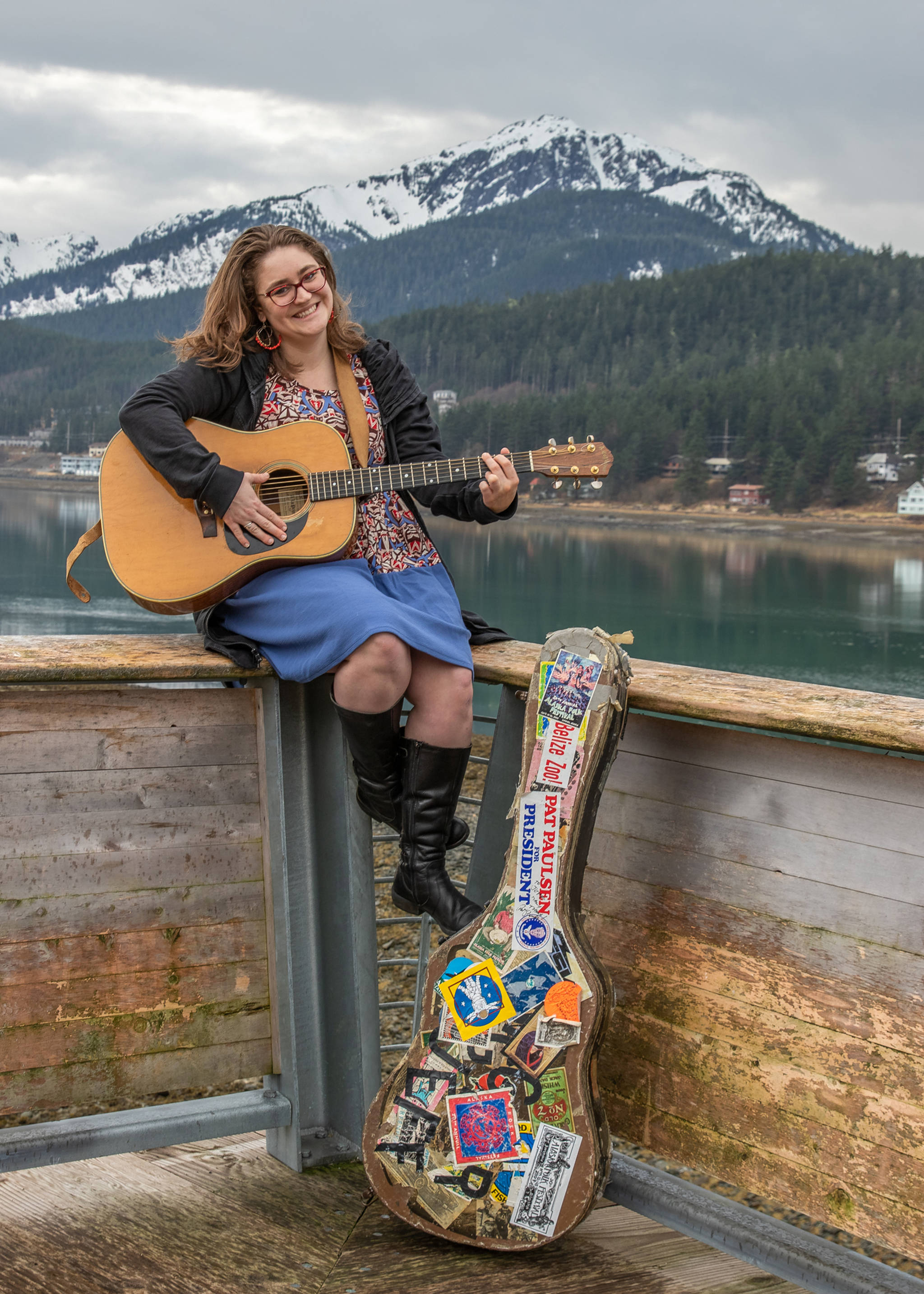April 14, 2019: The Alaska Folk Festival has a style all its own as does Callie Conerton. Callie first appeared on stage at this annual event when she was 2 years old and has played on stage there many times since. This day she wore a colorful empire waist dress from LuLaRoe, a black jacket from Prairie Grass, and black leather boots from Bos. & Co. Her essential accessories include her red glasses, red and gold beaded hoop earrings that her mom Maureen Conerton got while traveling, and an A LoPrinzi guitar that belongs to her dad Jeff Brown, which has been played in every Folk Fest since 1975.