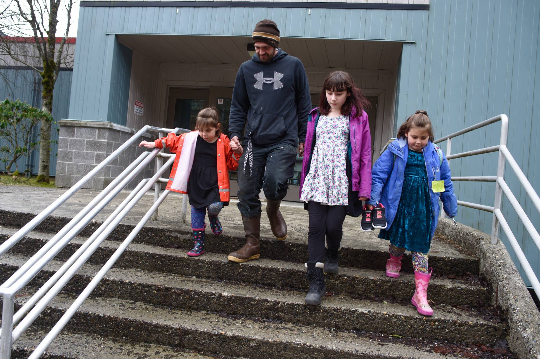 John Conklin picks up his children, Everlee, 5, left, Rhiana, 12, and Hazel, 7, from Juneau-Douglas High School: Yadaa.at Kalé after they were evacuated from the Marie Drake building on Friday, April 5, 2019. Flooding in a basement boiler room spread diesel fumes throughout the building. (Michael Penn | Juneau Empire)