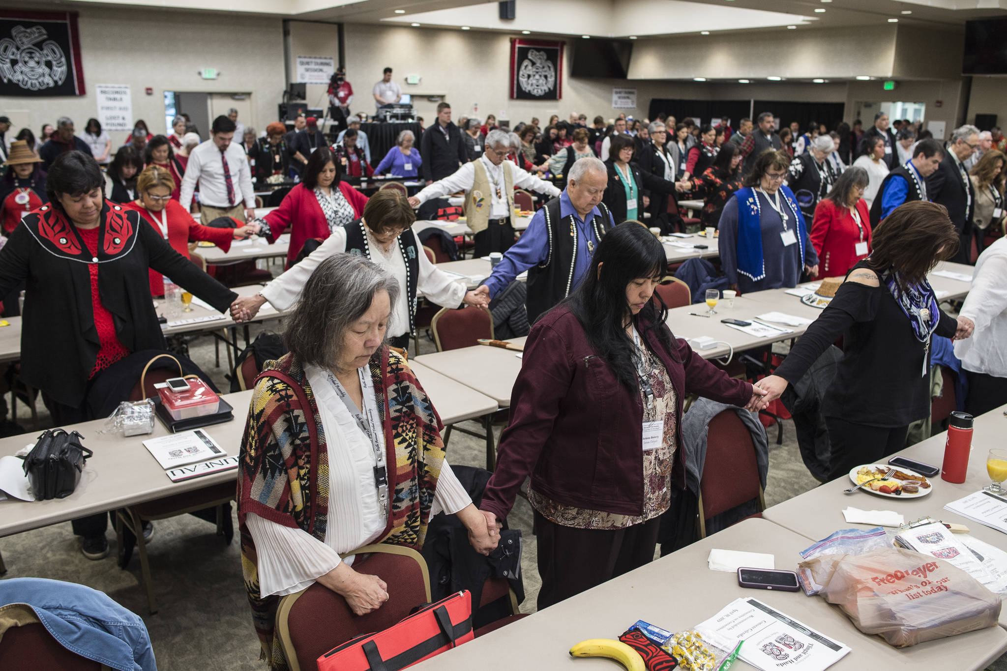 Deleagates listen to the invocation during the opening of the 84th annual Tribal Assembly of the Central Council of Tlingit and Haida Indian Tribes of Alaska at the Elizabeth Peratrovich Hall on Wednesday, April 10, 2019. (Michael Penn | Juneau Empire)