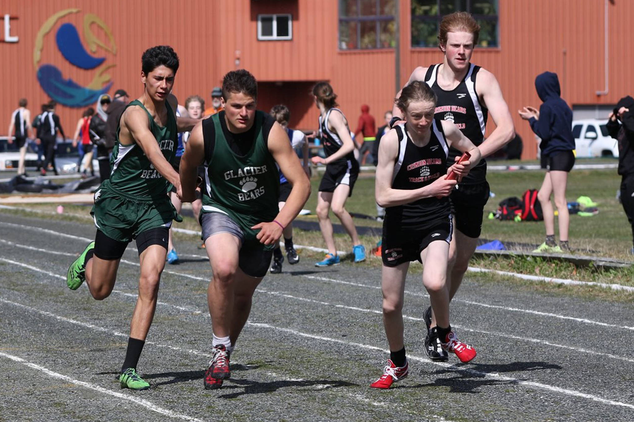 Juneau-Douglas High School's Aaron Blust, right, accepts the baton from Owen Squires during a relay race at the Haines Invitational in Haines last weekend. (Courtesy Photo | Lori Giddings)
