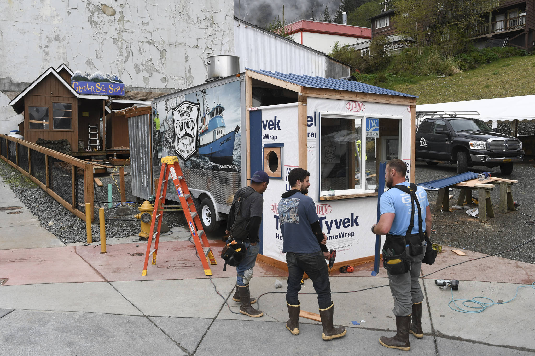 Dave McCasland, owner of Deckhand Dave's Fish Tacos, center, talks with Eric Plummer, left, and Brennen Brewer, of Peak Construction, as they set up food truck businesses at Gunakedeit Park, also known as Pocket Park, on Thursday, May 9, 2019. The businesses are expected to be open by Monday. (Michael Penn | Juneau Empire)