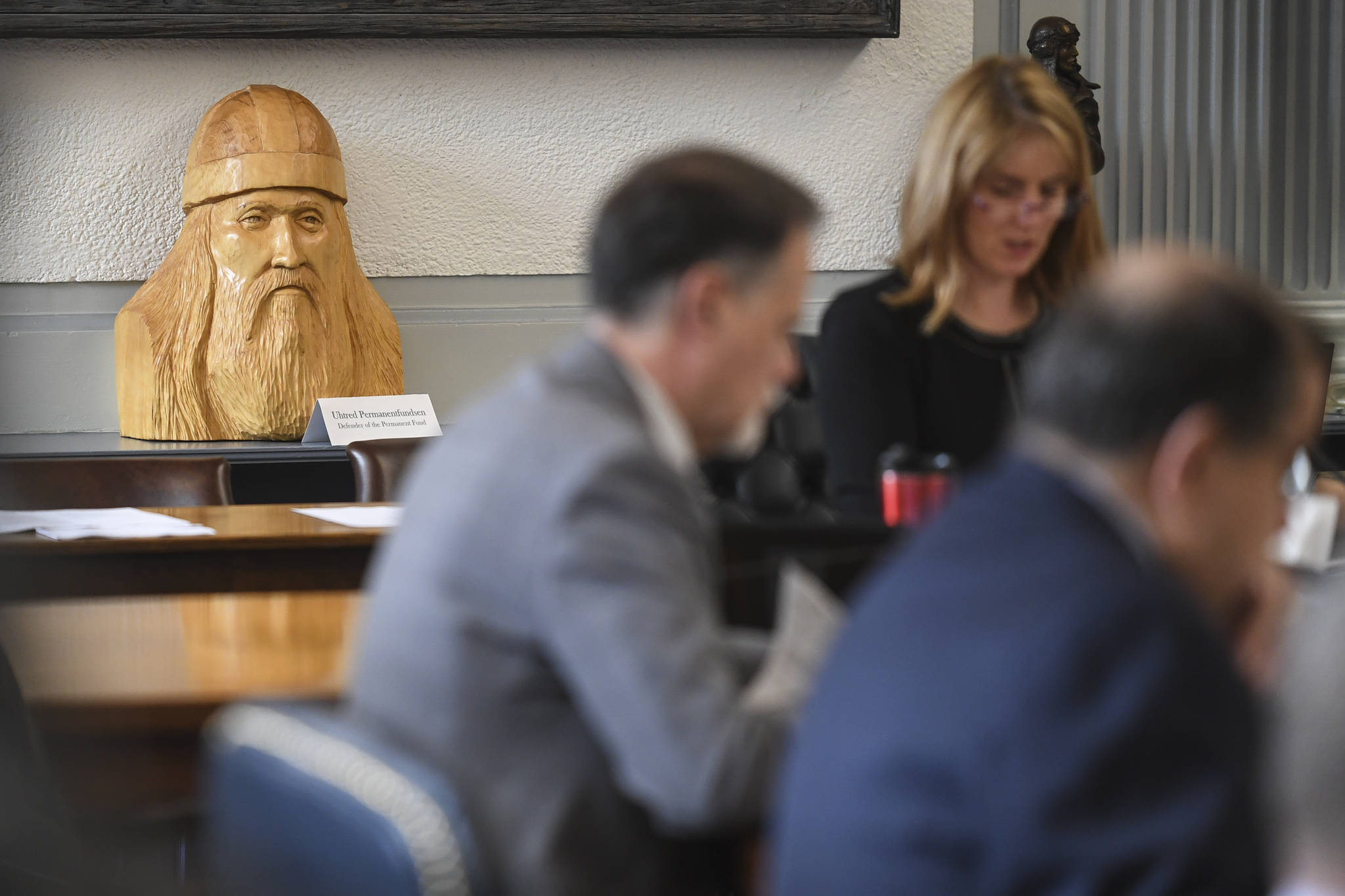 "A carved statue titled ""Uhtred Permanentfundsen, Defender of the Permanent Fund,"" sits on the counter as Sen. Natasha von Imhof, R-Anchorage, chairs the Senate Finance Committee at the Capitol on Monday, May 6, 2019. Co-Chair Bert Stedman, R-Sitka, bought the carving from Petersburg artist Robert Fudge recently and stationed it at the front of the Senate Finance Committee room. (Michael Penn 