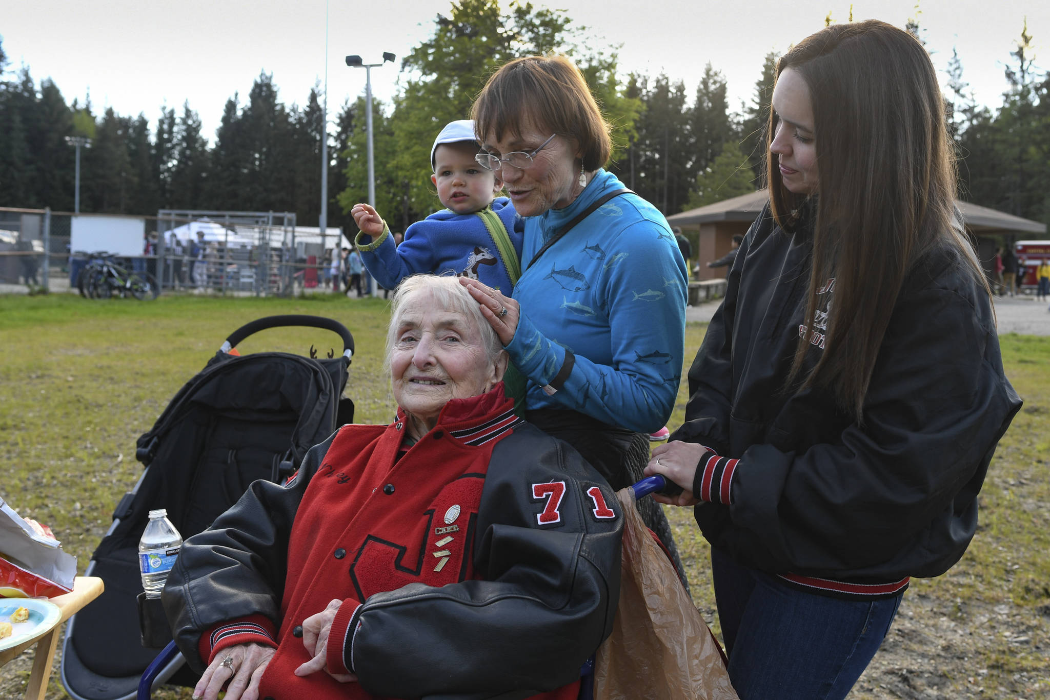 Charlotte Bain, 94, attends a tailgate party with her daughter, Claudia Bain, her granddaughter, Megan White, and her great-granddaughter, Louisa White, 21 months, before the Juneau Alumni Football Game with football players, dance team members and cheerleaders from Juneau-Douglas and Thunder Mountain High Schools at Adair-Kennedy Memorial Field on Friday, May 24, 2019. They were there to support Bain's grandson, James, who was playing for the Juneau Legends. White graduated in 2000. (Michael Penn | Juneau Empire)
