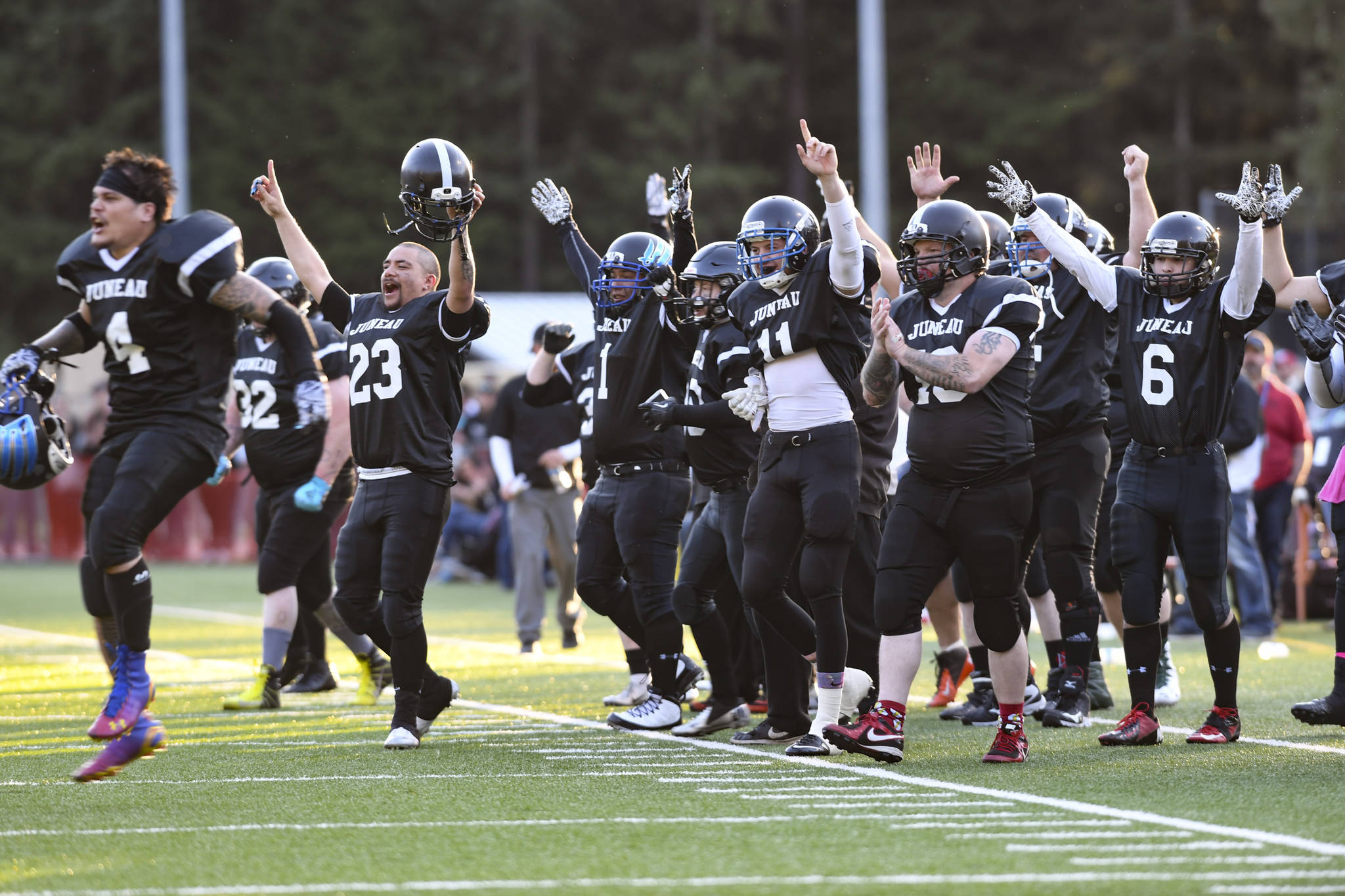 Legends players celebrate their first touchdown at the Juneau Alumni Football Game with football players, dance team members and cheerleaders from Juneau-Douglas and Thunder Mountain High Schools at Adair-Kennedy Memorial Field on Friday, May 24, 2019. (Michael Penn | Juneau Empire)