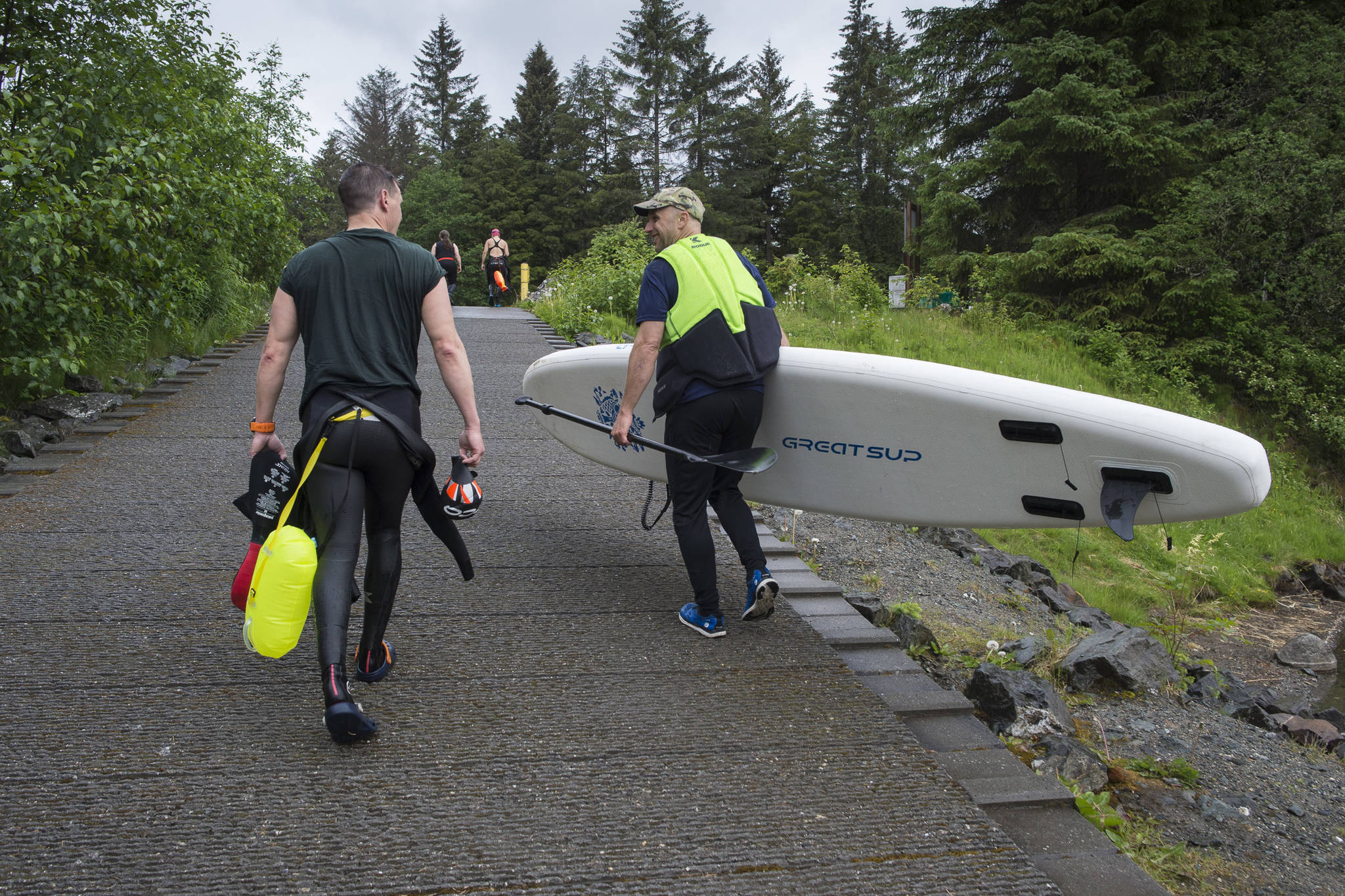 Scott Gende, left, and Kevin Sellers head up the ramp after swimmers trained in Auke Lake on Wednesday, June 5, 2019. (Michael Penn | Juneau Empire)