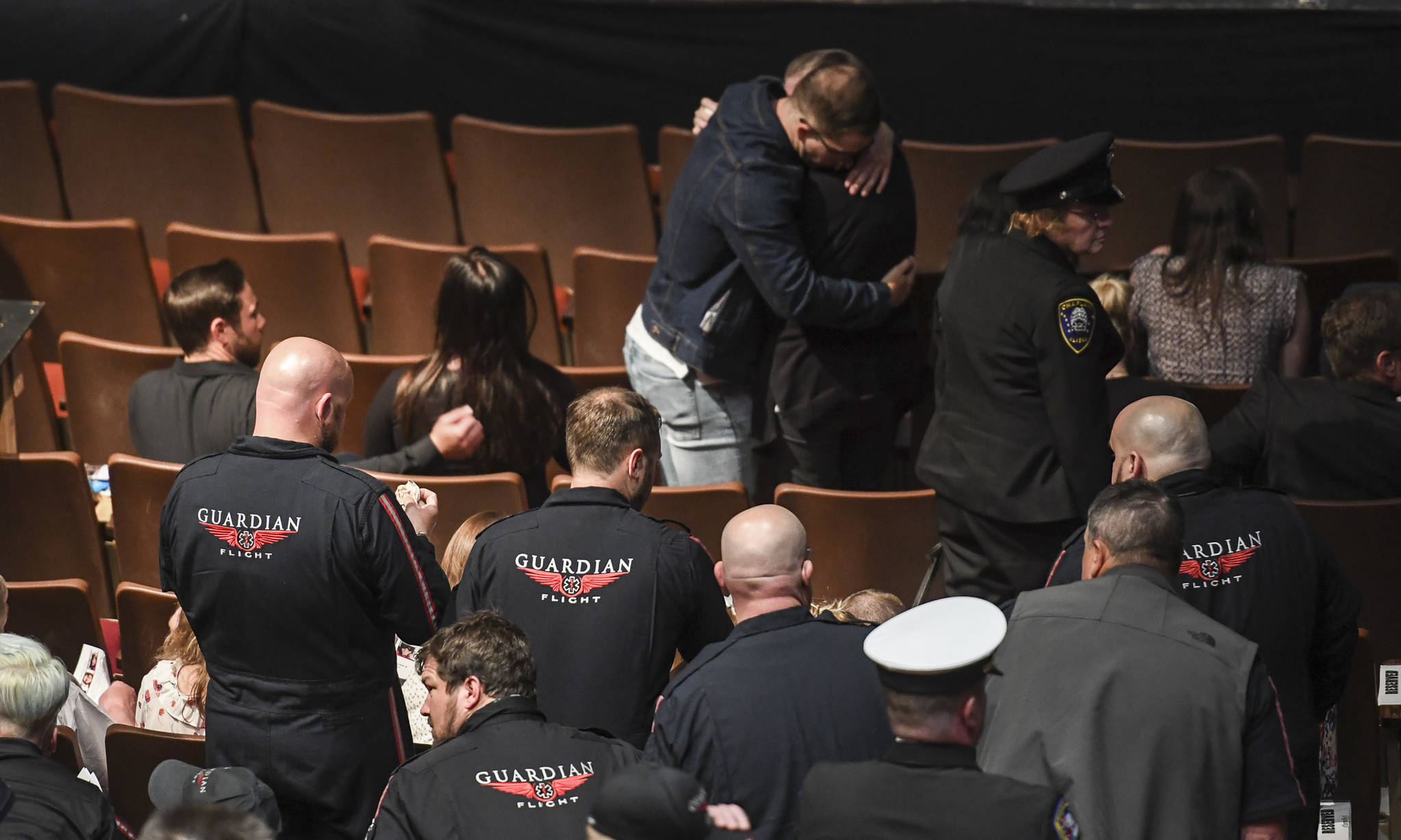 Family members embrace at the end of the a memorial service for the Guardian Flight crew held at Juneau-Douglas High School: Yadaa.at Kalé on Friday, June 7, 2019. (Michael Penn | Juneau Empire)