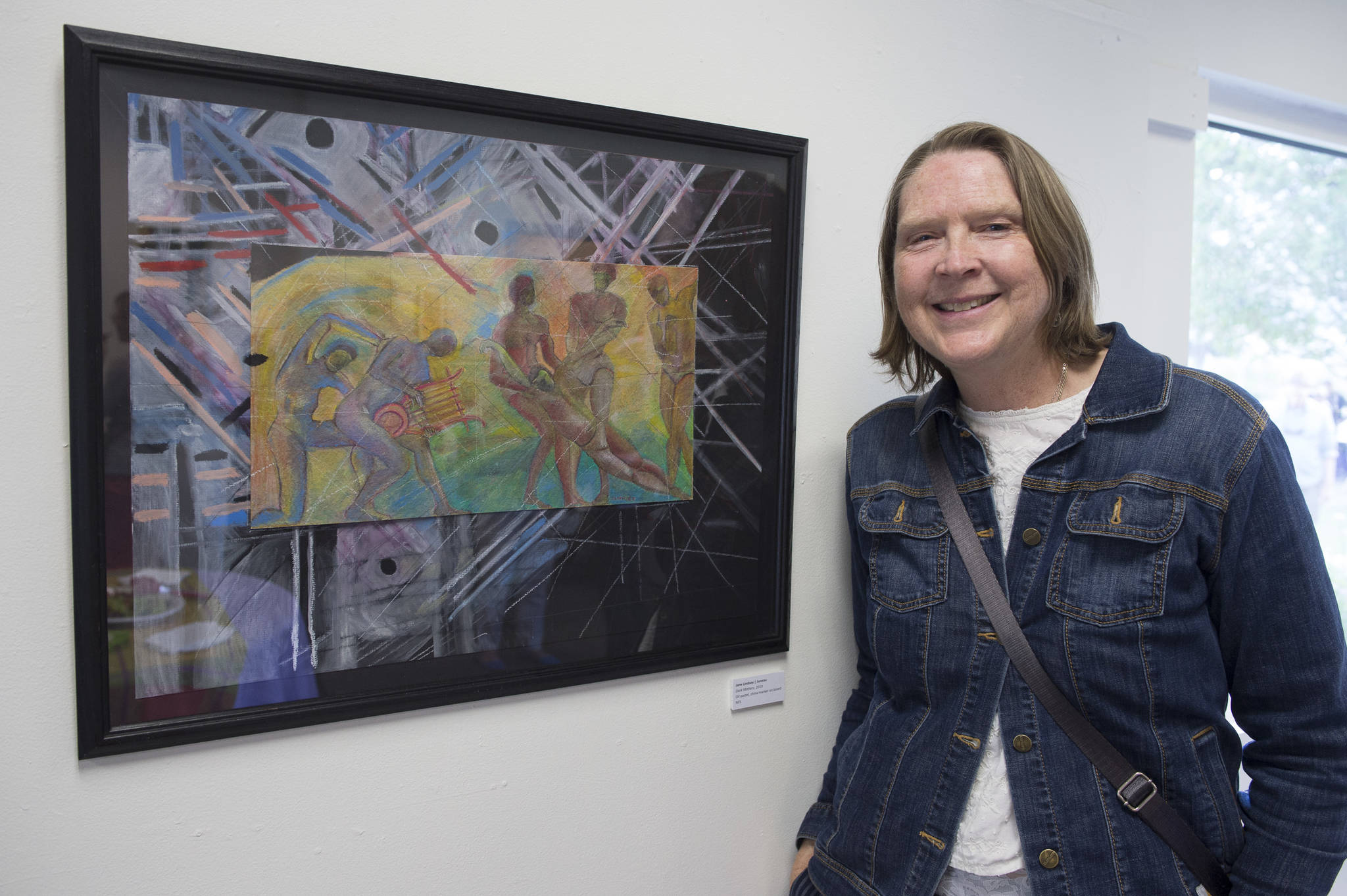 "Jane Lindsey stands next to her oil pastel and China marker painting ""Dark Matters"" in the Juneau Arts and Humanities Council's Juried Art Show for First Friday on Friday, June 7, 2019. (Michael Penn 