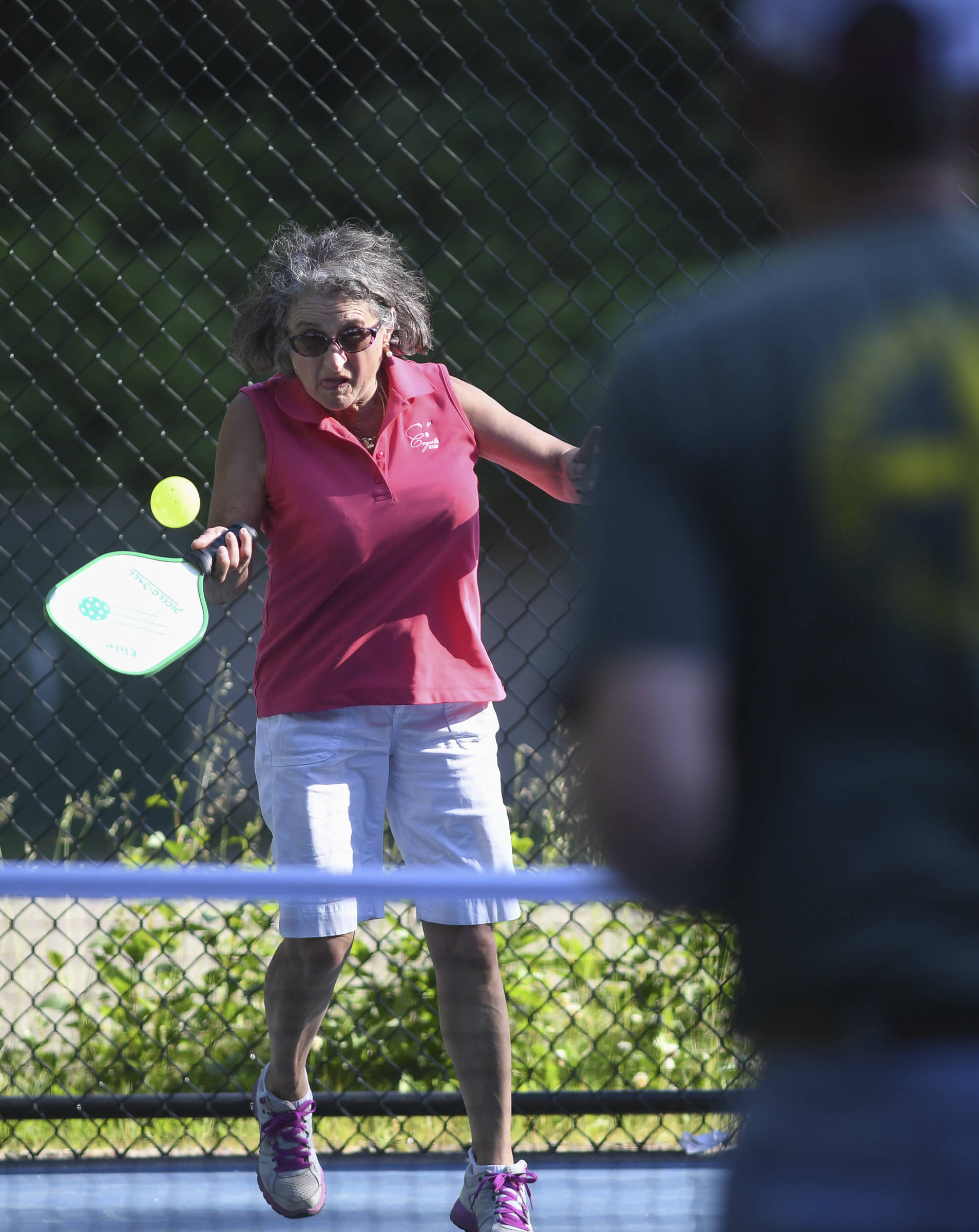 Orlinda Kittredge plays the ball during a pickleball match at the Cope Park tennis courts on Wednesday, June 26, 2019. (Michael Penn | Juneau Empire)