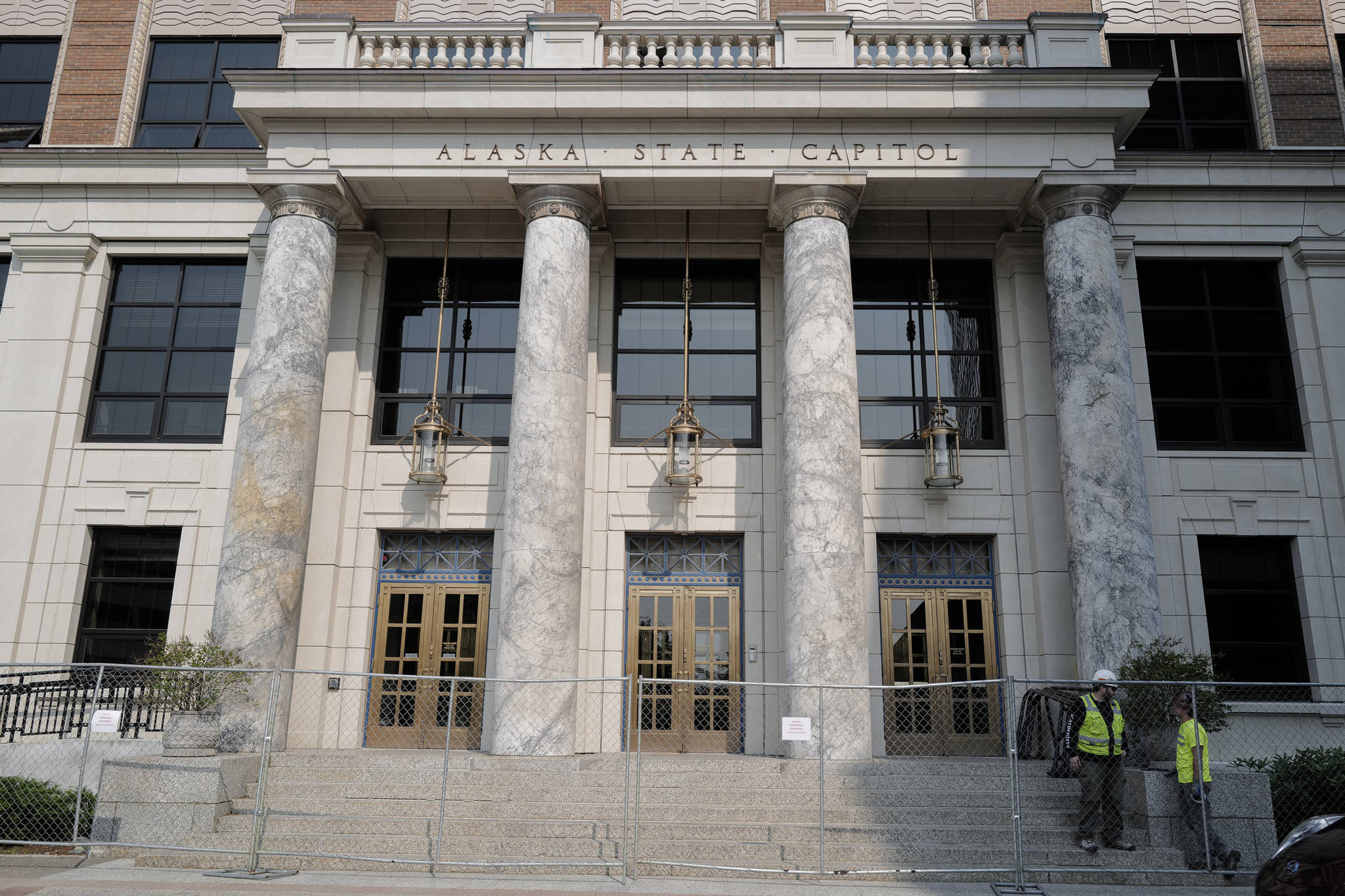 Fencing is installed in front of the Alaska State Capitol on Tuesday, July 2, 2019. The marble pillars, quarried in Tokeen, Alaska, will be sealed and ground smooth as part of the building's remodeling project. (Michael Penn   Juneau Empire)