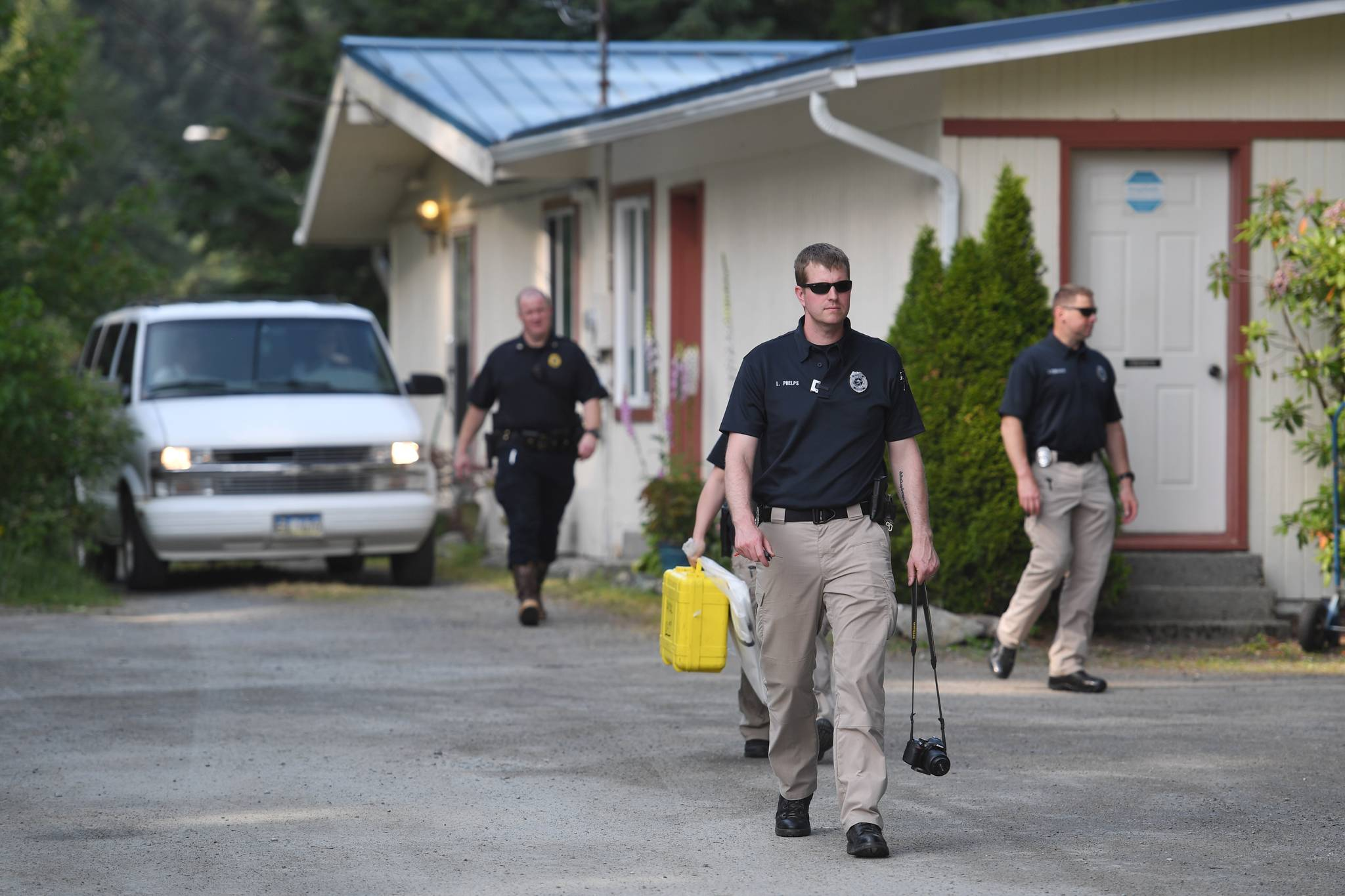 JPD detectives leave 9010 Atlin Drive as a body is driven away on Wednesday, July 3, 2019. (Michael Penn | Juneau Empire)