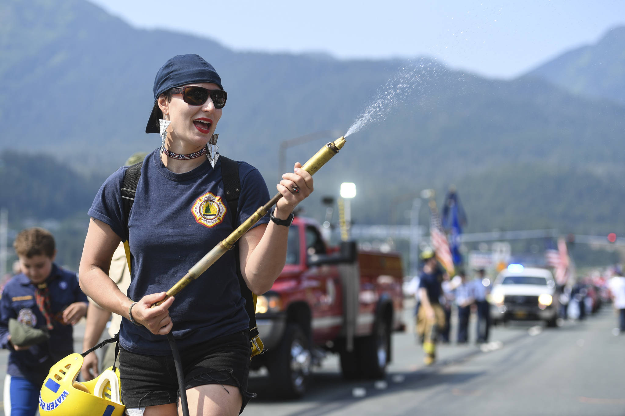 Meghan DeSloover of Capital City Fire/Rescue keeps poeple cool during the Juneau Fourth of July Parade on Thursday, July 4, 2019. (Michael Penn | Juneau Empire)