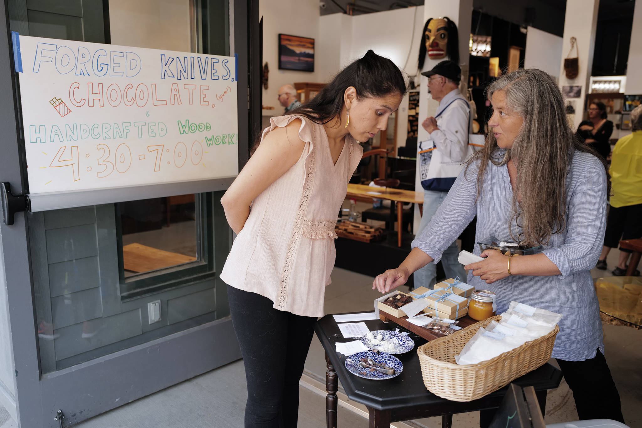 Marta Lastufka, right, owner of Sweet Song Chocolates, shows her wares to Elia Salinas during First Friday at Rainforest Designs on South Franklin Street on Friday, July 5, 2019. Lastufka was one of three featured artists at the local artisans shop. Wood worker Henry Webb and knife maker Liam Penn were also featured. (Michael Penn | Juneau Empire)
