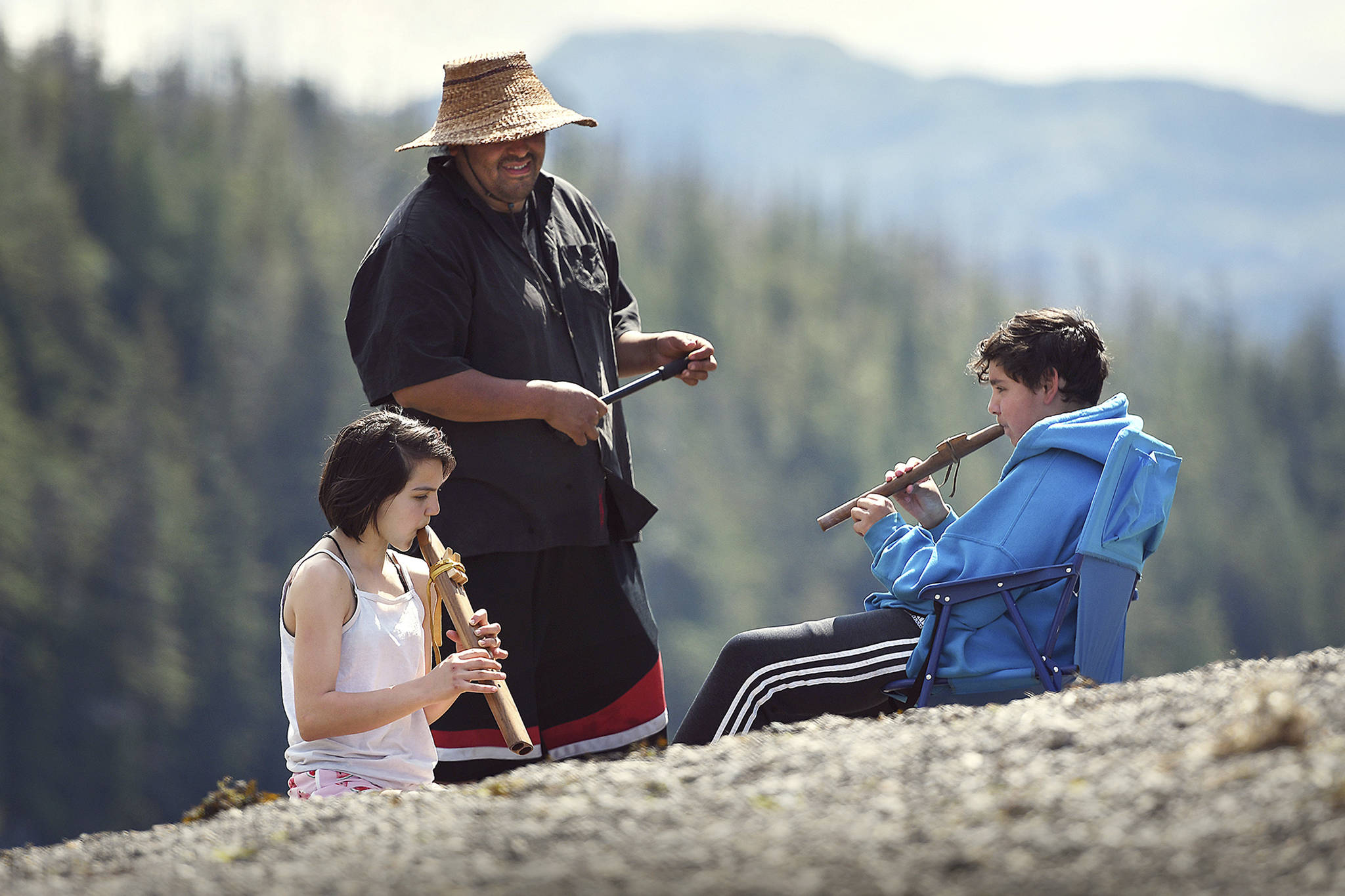 In this photo taken June 20, 2019, Sophie Lynda Agoney, 13, and Alexander Orion Shull, 12, both of Ketchikan, learn how to play the native flute from mentor Johon Atkinson during Culture Camp on Hemlock Island near Metlakatla, Alaska. This year was the first time the Ketchikan Indian Community and Nüüm Na Waalt culture camps joined together for the event and a seven-night campout on the island. (Dustin Safranek/Ketchikan Daily News via AP)