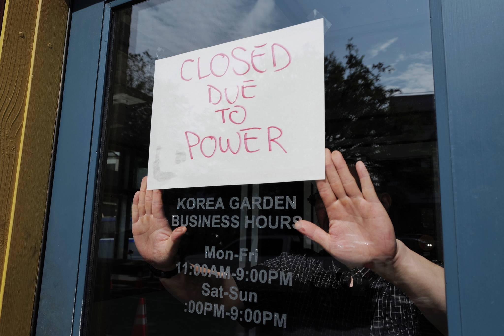 Steven DeVoss, manager of Korea Garden on Front Street, puts up a sign to closed his business before noon on Wednesday, July 31, 2019. (Michael Penn | Juneau Empire)