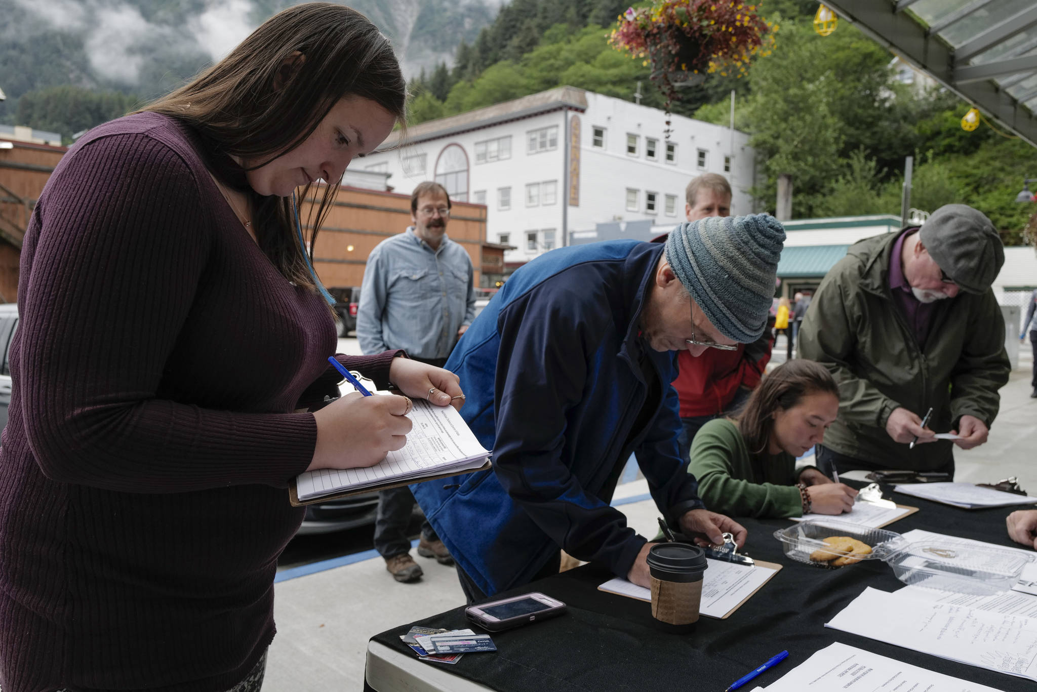 Monika Kunat, left, signs an application petition to recall Gov. Mike Dunleavy with others at the Planet Alaska Gallery on Thursday, Aug. 1, 2019. (Michael Penn | Juneau Empire)