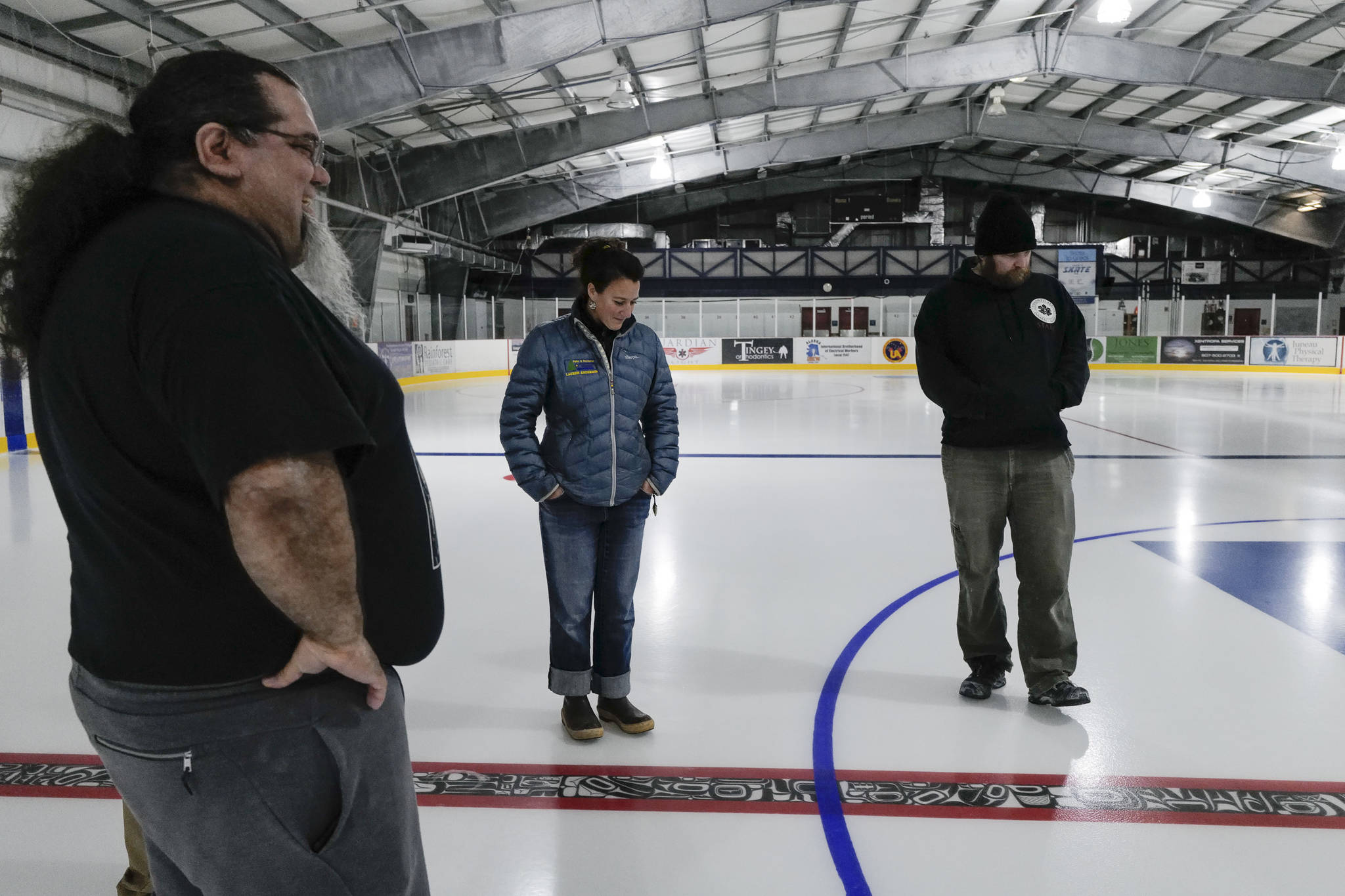 Tsimshian artist Abel Ryan Tsimshian, left, talks Treadwell Arena Manager Lauren Anderson, center, and Program Coordinator Thomas McKenzie about the red line at the Treadwell Arena on Thursday, August 1, 2019. Ryan worked with students in the BAM After School Program to draw animals in Northwest Coast formline designs to be incorporated in the hockey rink ice. The Treadwell Arena opens for the season on Monday. (Michael Penn | Juneau Empire)