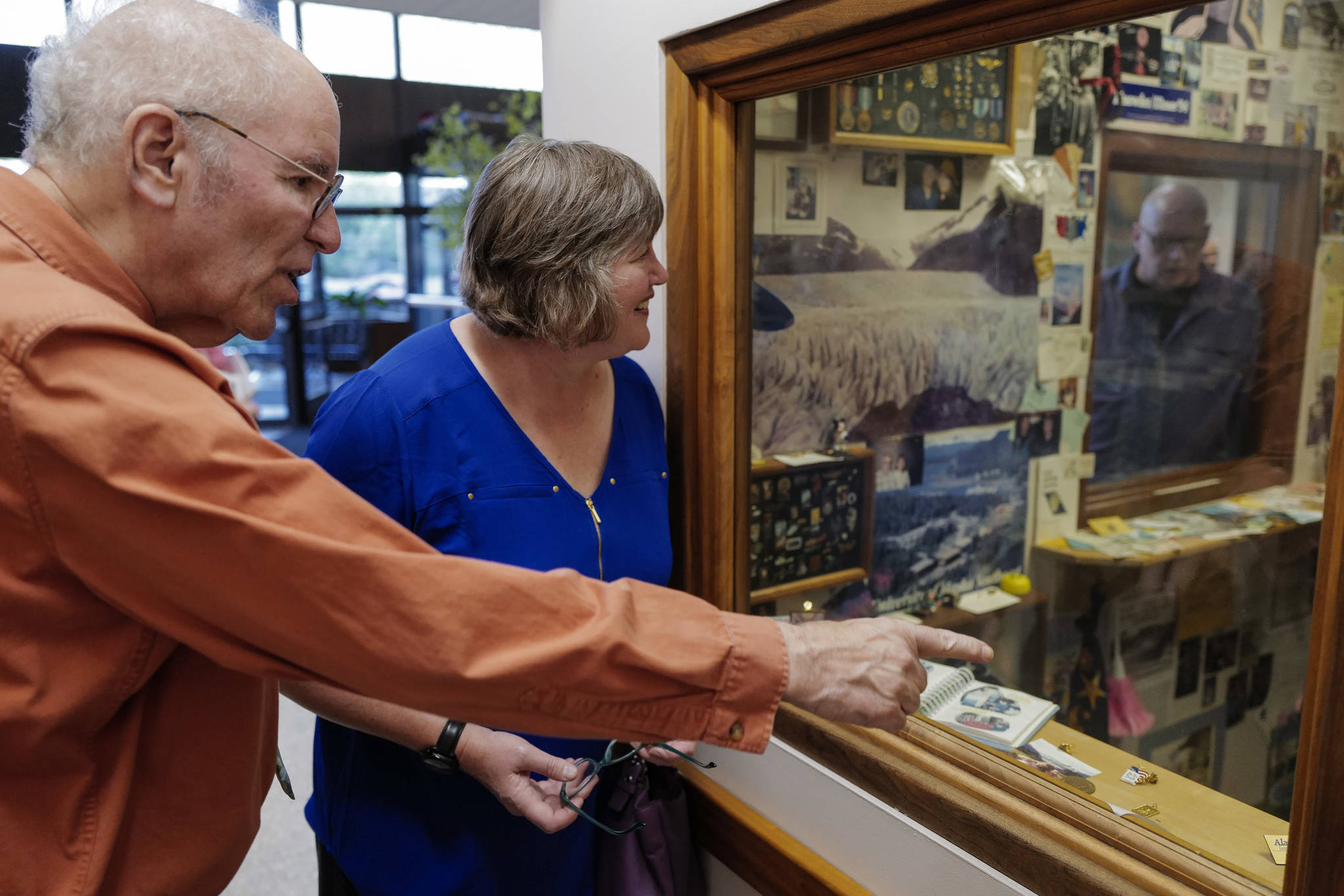 Michael Orelove, left, talks with Rep. Sara Hannan, D-Juneau, as they look at items on the 25th anniversary of the 1994 Juneau Time Capsule at the Hurff Ackerman Saunders Federal Building in Juneau on Friday, Aug. 9, 2019. Mark Farmer, right, looks in through a second window. Ovelove was on the committee that set up the capsule which is set to be opened at the 100 year mark. (Michael Penn | Juneau Empire)