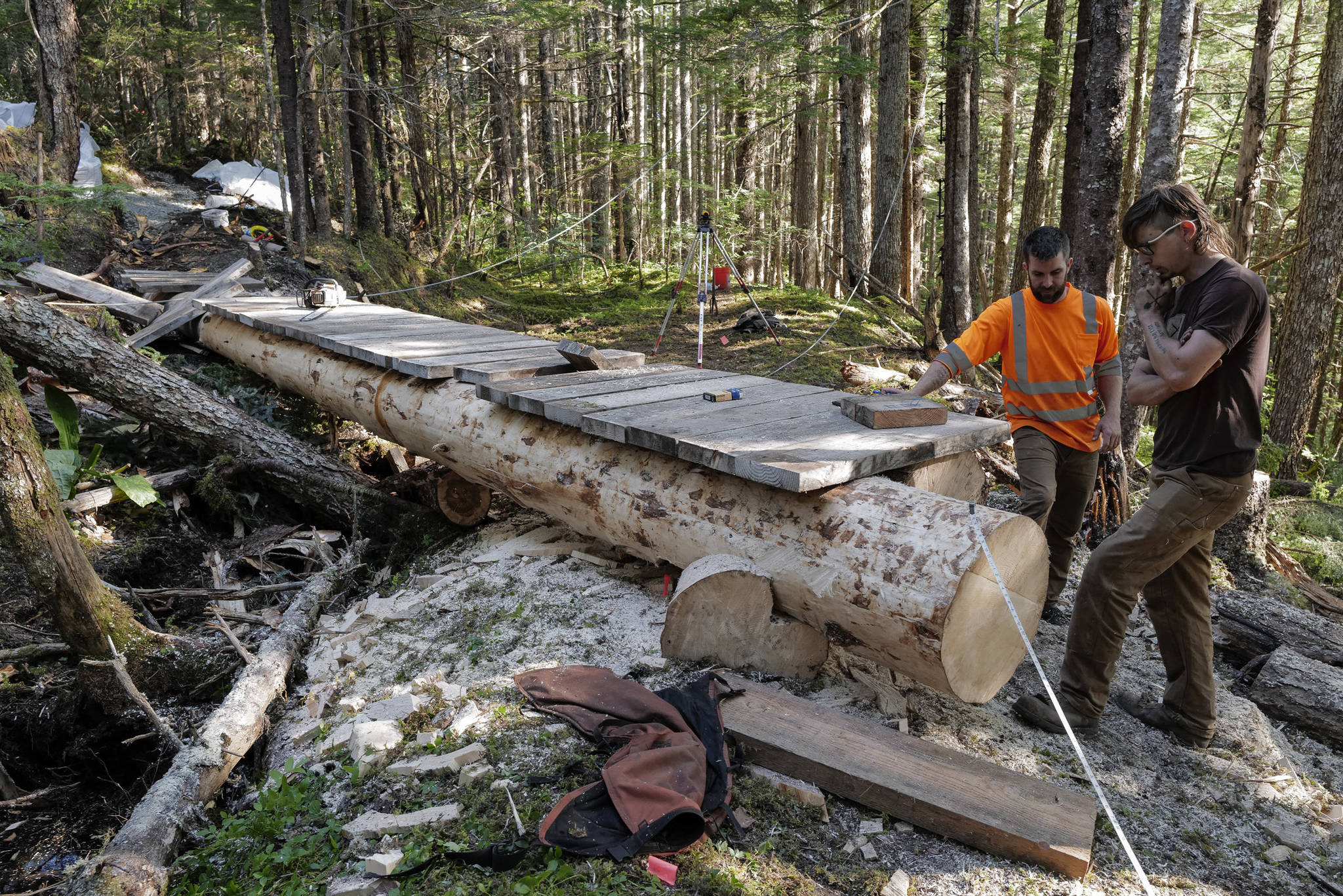 Crew leader Duncan Campbell, right, and Trail Mix Project Manager Ryan O'Shaughnessy work on a log bridge for a new Treadwell Gorge reroute trail on the Treadwell Ditch Trail on Thursday, Aug. 8, 2019. (Michael Penn | Juneau Empire)