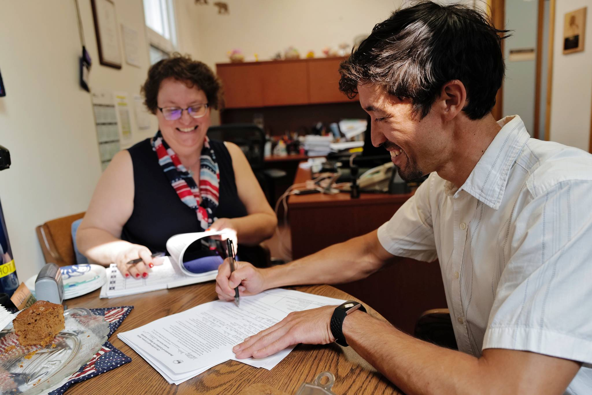 Greg Smith signs his application in front of Municipal Clerk Beth McEwen on Monday, Aug. 12, 2019, to run for one of two Assembly District 1 seats in this falls municipal election. (Michael Penn | Juneau Empire)