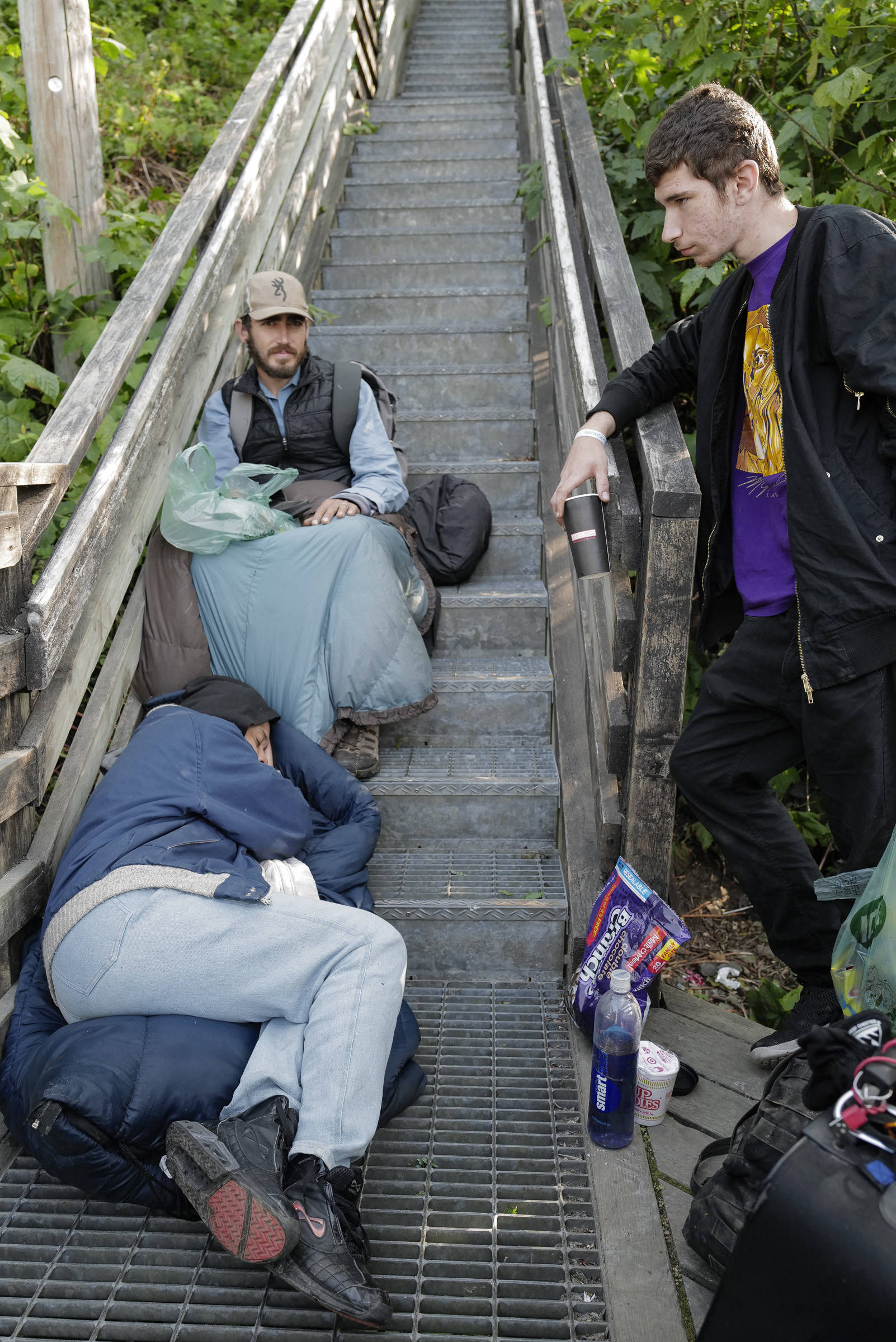 Homeless people spend their time on the Decker Way stairs after the Glory Hall's closure on Tuesday, Aug. 13, 2019. (Michael Penn | Juneau Empire)