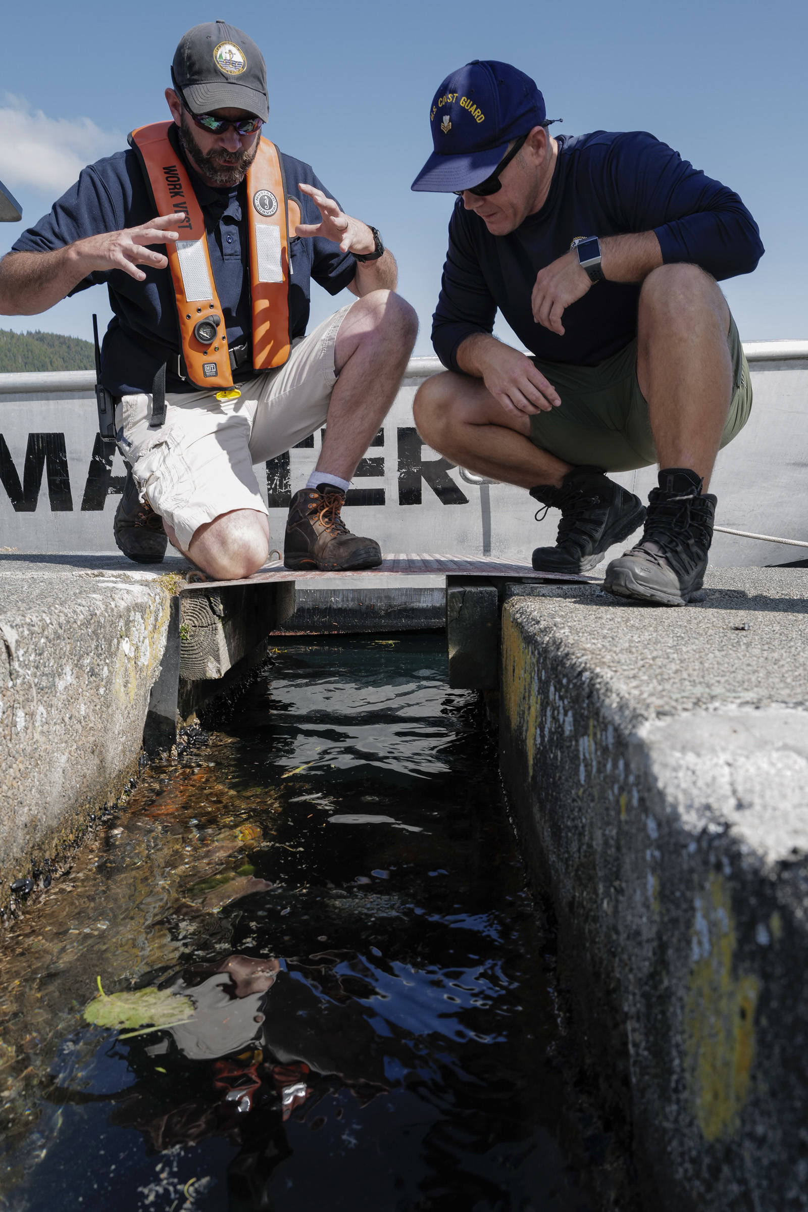 Deputy Harbormaster Matt Creswell, left, explains to the project to Shawn Price, of U.S. Coast Guard Regional Dive Locker West, at the Don D. Statter Boat Harbor in Auke Bay on Friday, Aug. 16, 2019. Members of the U.S. Army's 74th Engineer Dive Detachment and U.S. Coast Guard Regional Dive Locker West worked together to inspect and replace the bolts holding the harbor's breakwater together. (Michael Penn | Juneau Empire)