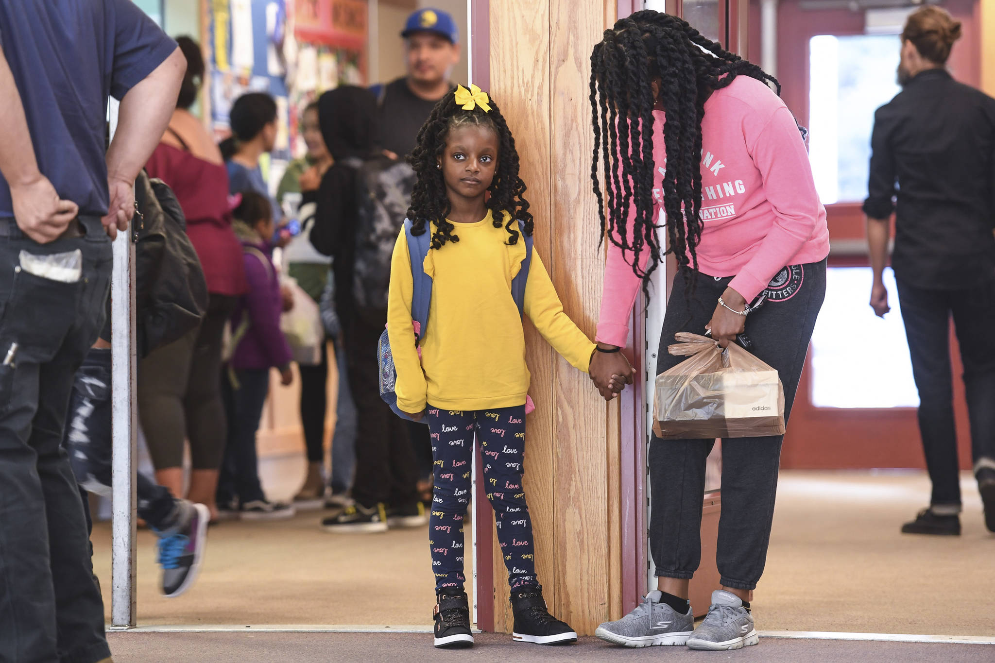 Ariyah Allen, holds hands with her mother, Odette, after arriving for the first day of school at Riverbend Elementary School on Monday, Aug. 19, 2019. (Michael Penn | Juneau Empire)