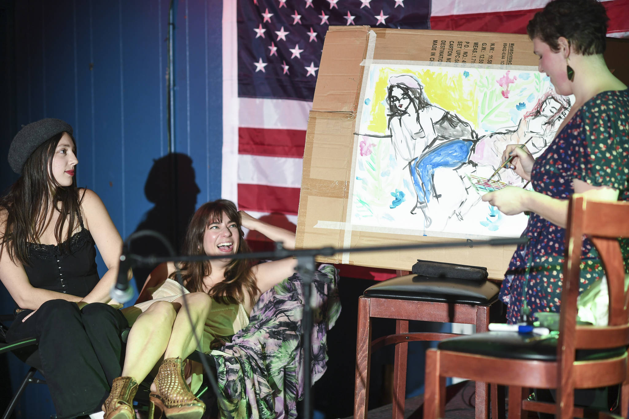 Natalie Weinberg, right, performs with a live model painting of Dana Herndon, center, and Serena Drazkowski during the GRLZ open mic night at the The Rendezvous Bar on Wednesday, Aug. 14, 2019. (Michael Penn | Juneau Empire)