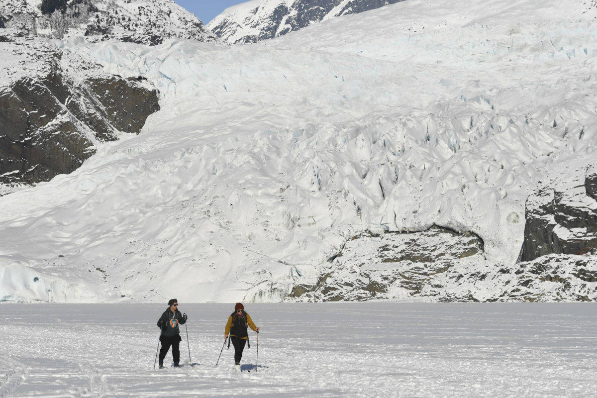 Sam Post, left, and Lydia Steele ski back from a visit to the Mendenhall Glacier on Monday, Feb. 11, 2019. (Michael Penn | Juneau Empire)