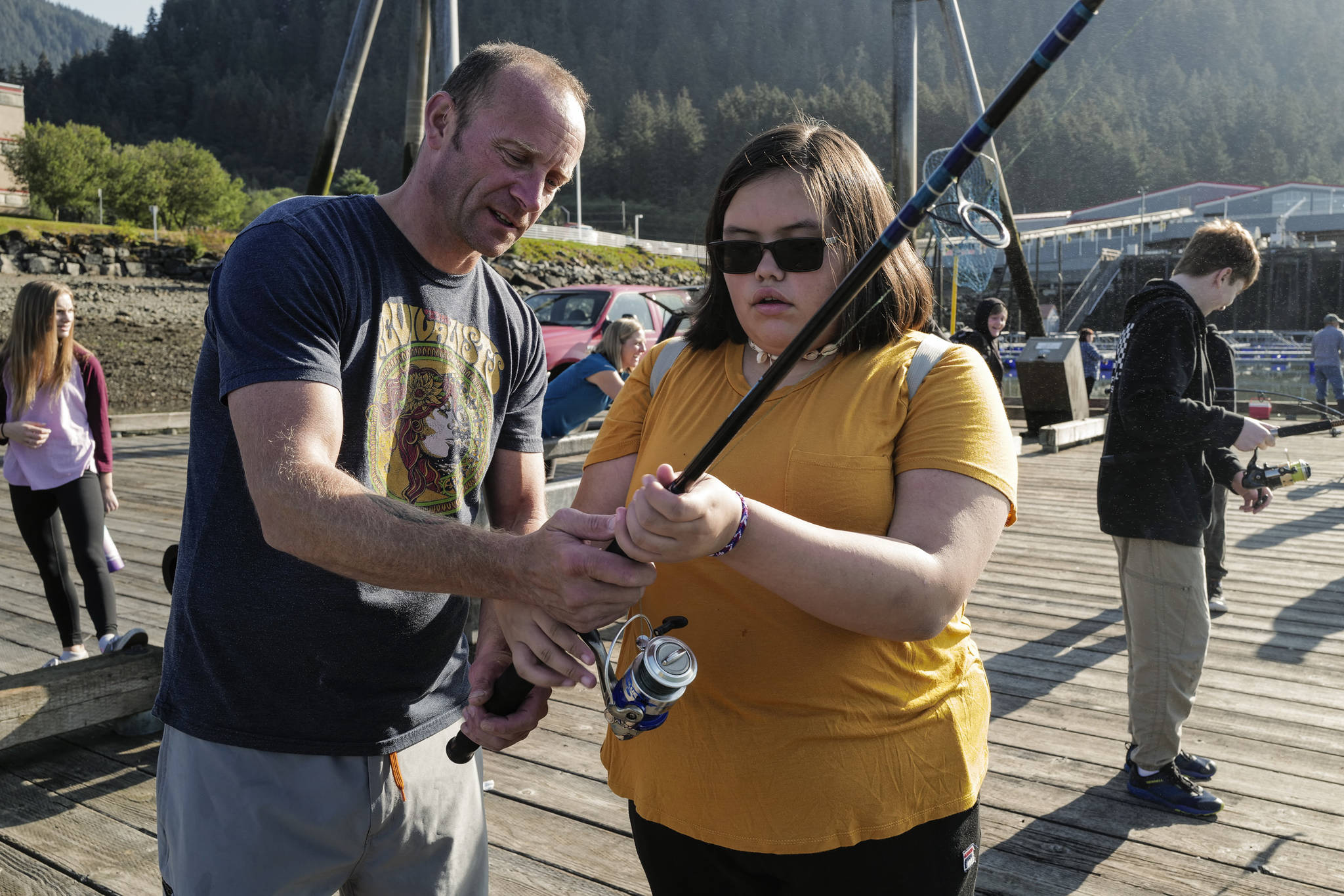 Dzantik'i Heeni Middle School eighth-grader Jaylynn Martin, right, is helped by Teacher Bobby Jones while fishing for salmon at the Wayside Park on Channel Drive on Friday, Aug. 30, 2019. The fish will be used in a dog treat business the students are developing to raise money for a water filtering system to be used at the school. Two math teachers, Jones and Tennie Bentz, are having the students start four businesses as a way of teaching the use of math in the real world. (Michael Penn | Juneau Empire)