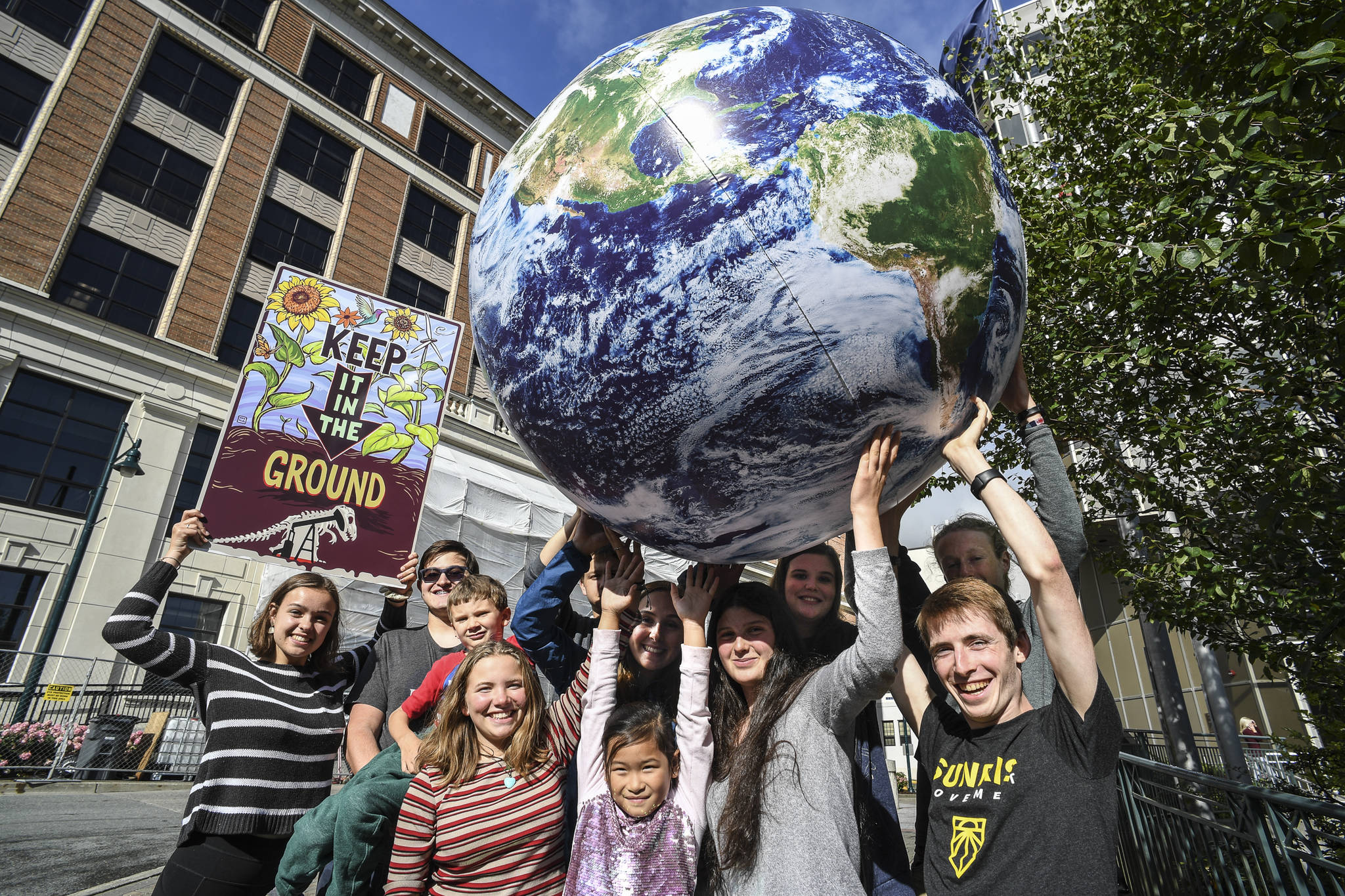 """Students associated with 350 Juneau, a local chapter of an international grassroots climate movement, meet Tuesday, Sept. 3, 2019, in front of the Alaska State Capitol. They promoted a """"Stand Strong for Climate Rally"""" to be held Tuesday, Sept. 10 at noon in front of the Capitol. (Michael Penn 