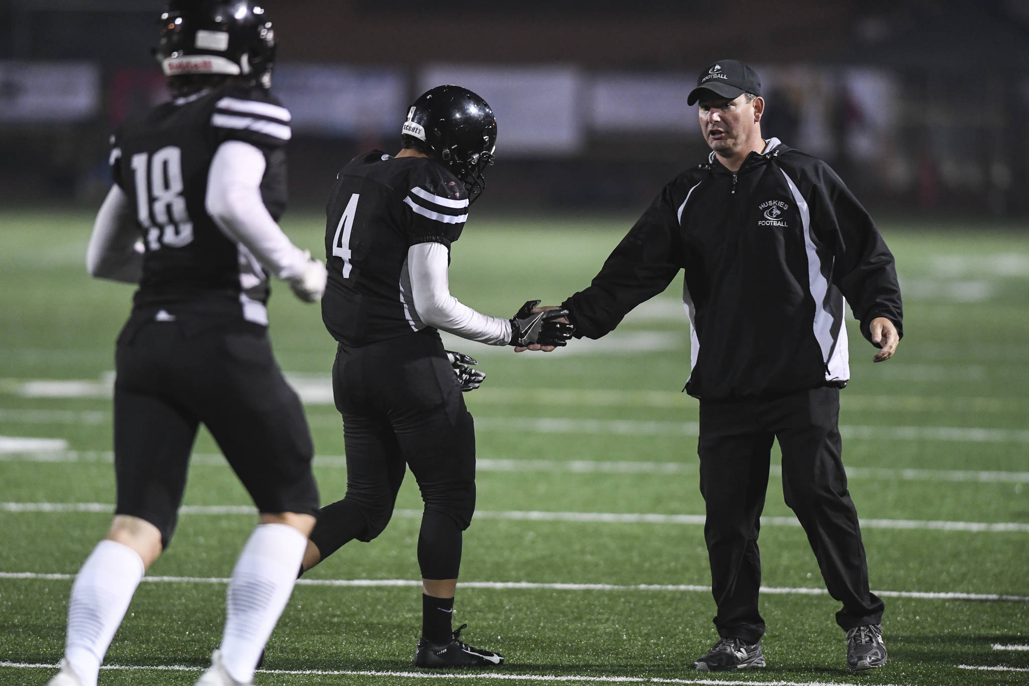 Juneau's head coach Rich Sjoroos congratulates Ali Beya, center, and Cooper Kriegmont in the third quarter as they compete against Wasilla at Adair-Kennedy Memorial Field on Friday, Sept. 6, 2019. Juneau won 63-0. (Michael Penn | Juneau Empire)